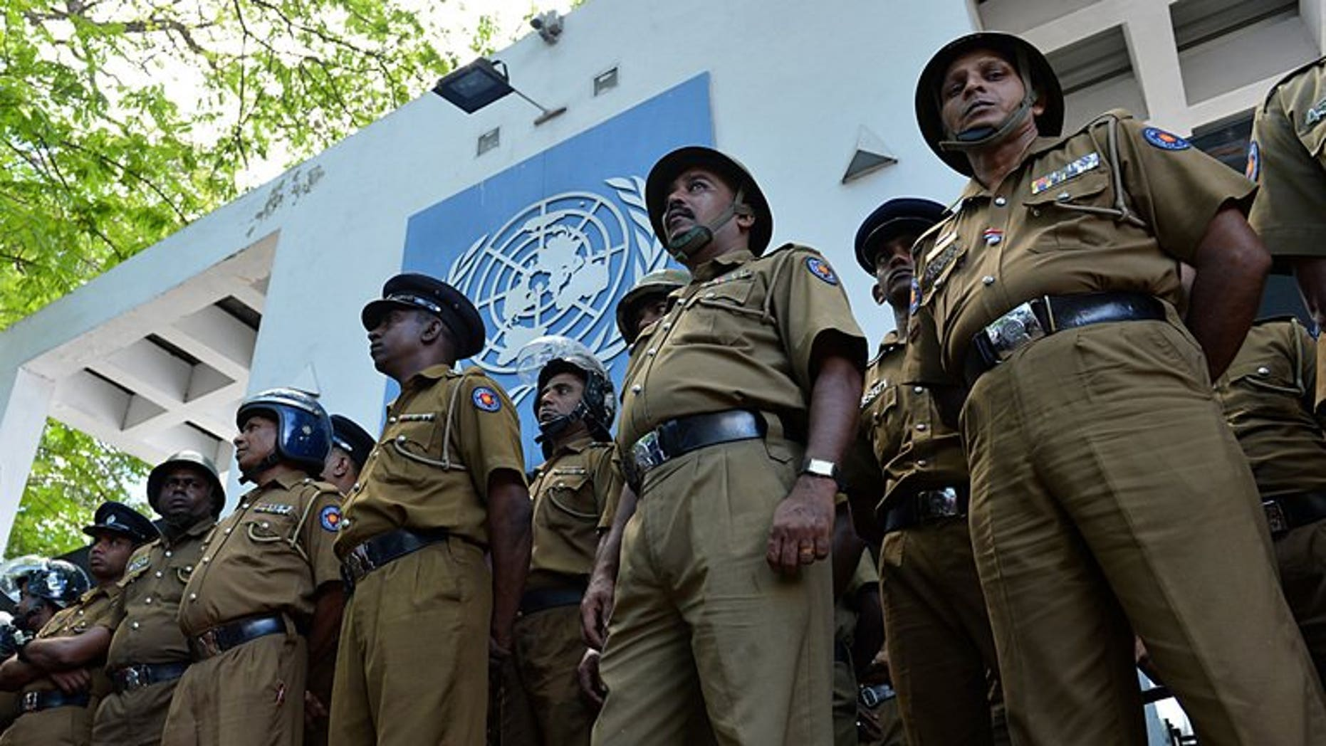 Sri Lankan police stand guard outside the UN office in Colombo on August 31, 2013. Sri Lankan police have arrested a navy officer suspected of involvement in smuggling people in fishing boats to Australia, officials said Saturday.