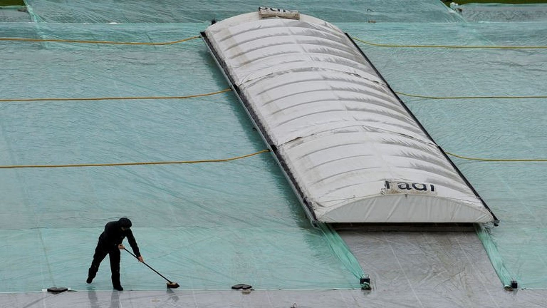 Staff work on the covers as rain delays the start of the first one day international match between England and Australia in Leeds, England, on September 6, 2013. Australia vice-captain George Bailey is praying the Manchester weather will not stop his side from giving England a tough time at Old Trafford.