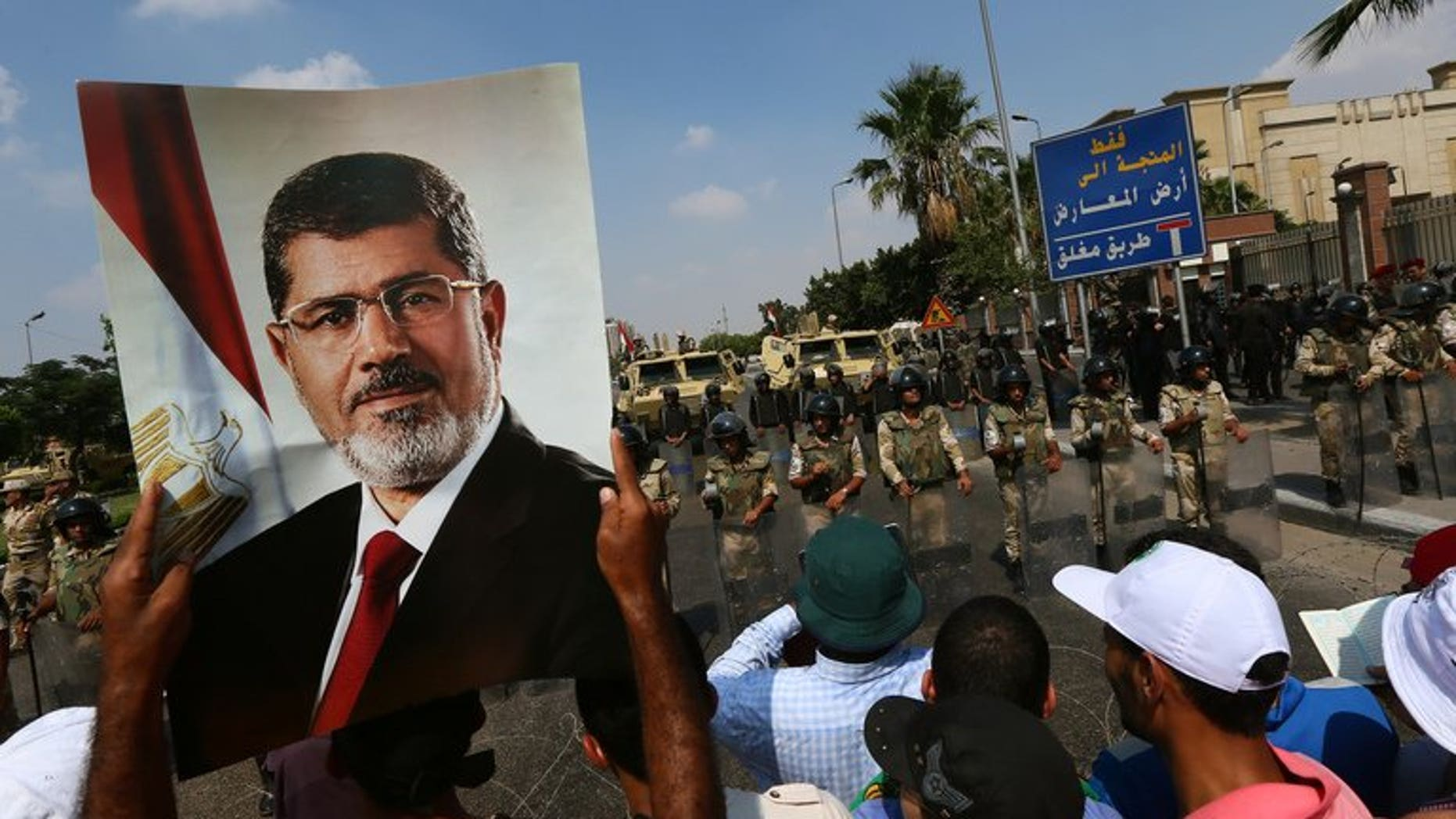 A supporter of ousted Egyptian president Mohamed Morsi holds a picture of the toppled leader in Cairo, on July 19, 2013. An Egyptian prosecutor has levelled new accusations against Mohamed Morsi, already facing trial on other charges, alleging the Islamist had insulted the country's judiciary when he was president, media reported.