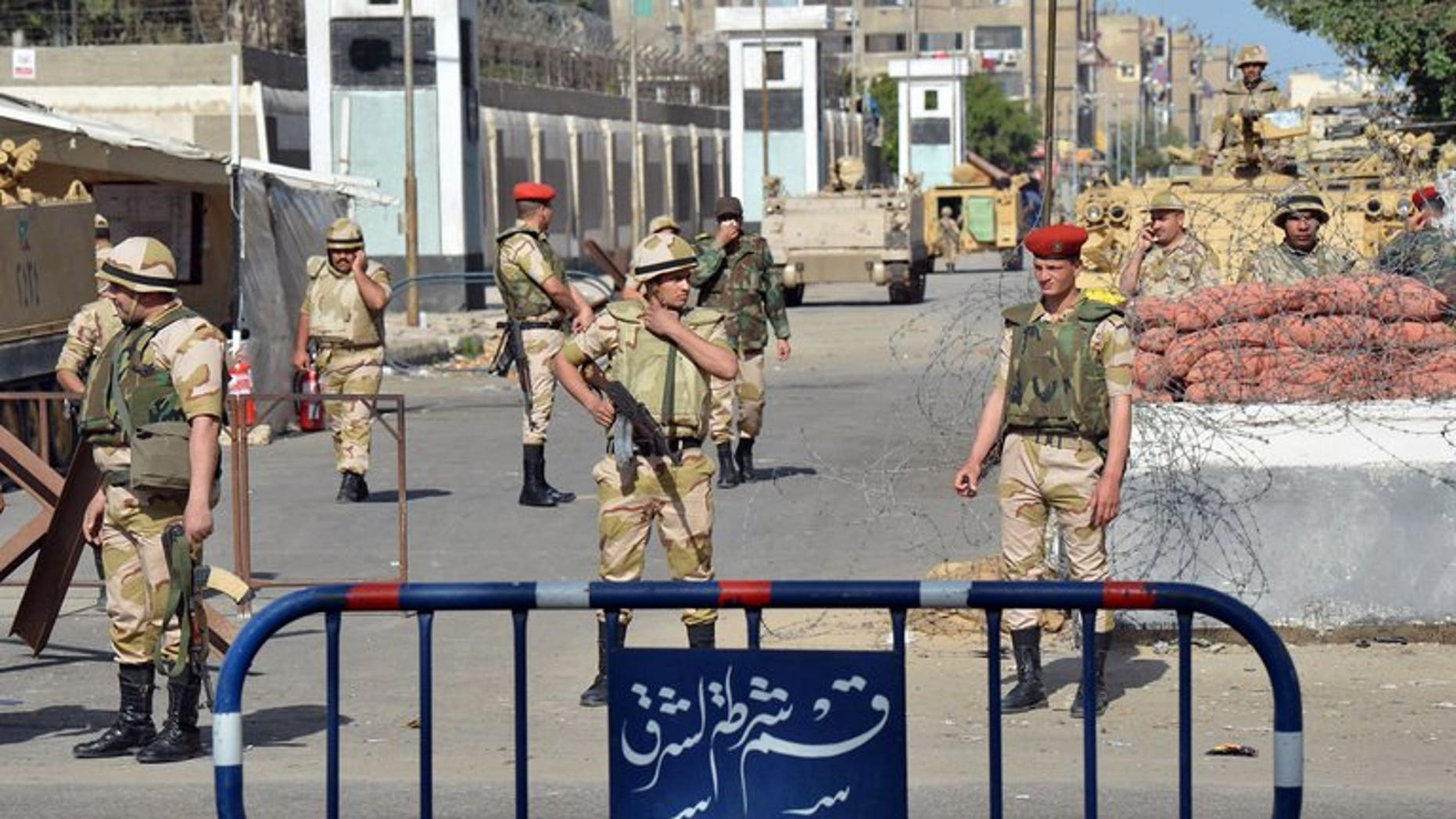 Egyptian soldiers stand guard in front of a prison in the Suez Canal city of Port Said on March 9, 2013. Egyptian military engineers have defused mortar rounds rigged to explode on a railroad linking the canal cities of Ismailiya and Suez, security officials said.