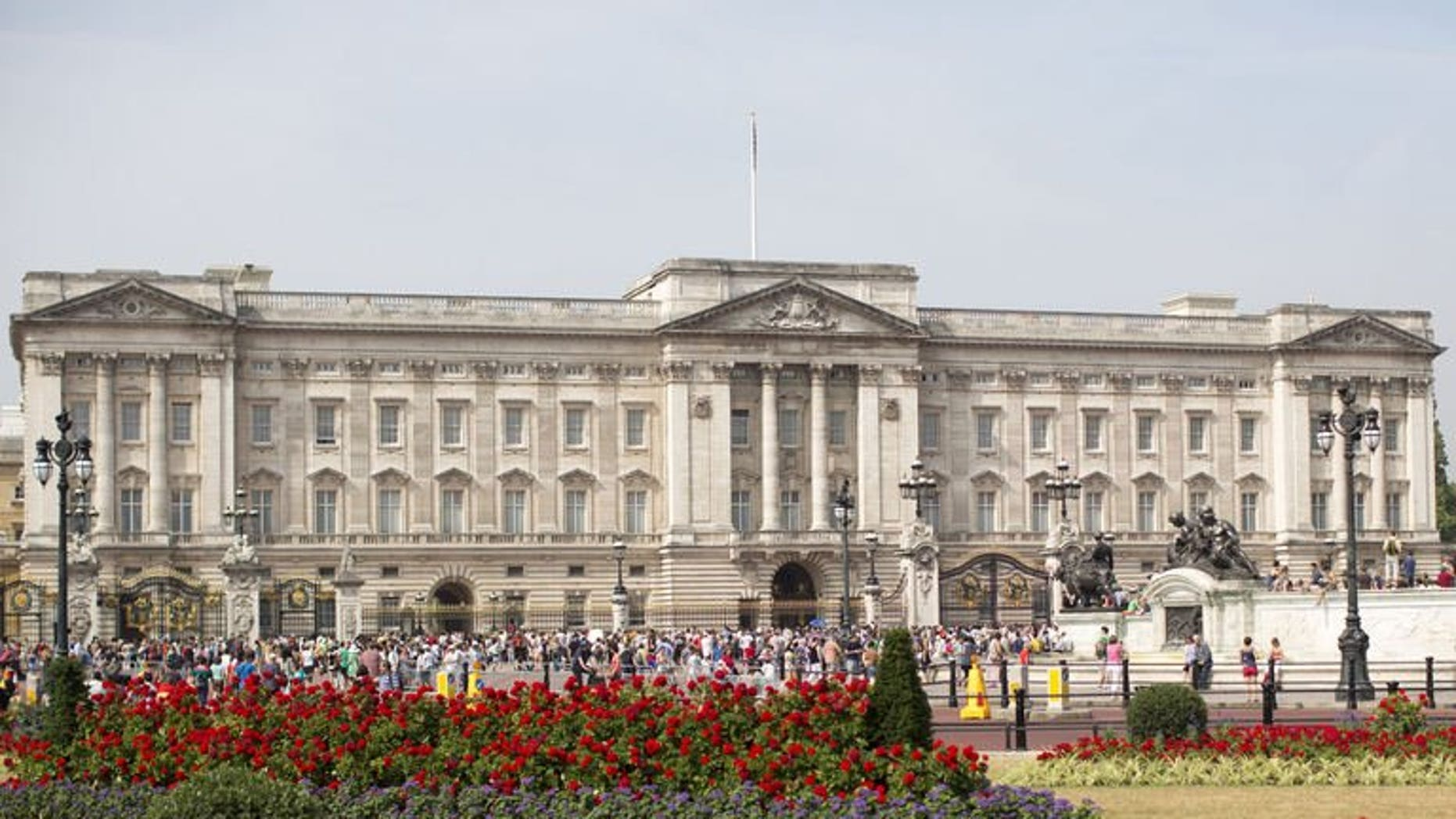 Tourists gather outside Buckingham Palace in central London on July 22, 2013. British police said they had arrested a man who scaled a fence to get into the palace, the official London residence of Queen Elizabeth II.
