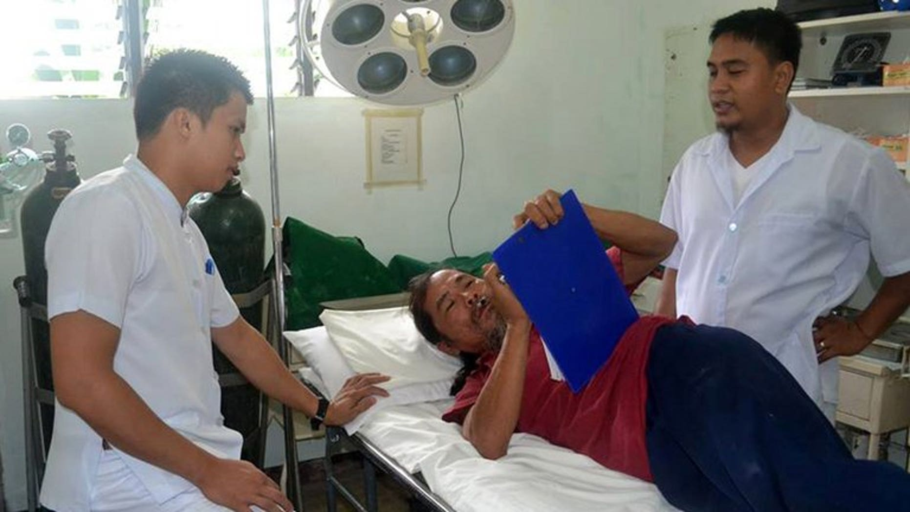 In this handout photo taken on September 4, 2013, Taiwanese fisherman Tsai Po, 54 (centre) is attended to by medical personnel at the Batanes General Hospital, on September 4, 2013. Philippine police say there is strong evidence to charge Tsai -- detained after he strayed into the archipelago's waters -- in an incident that is threatening reviving relations between the neighbours.