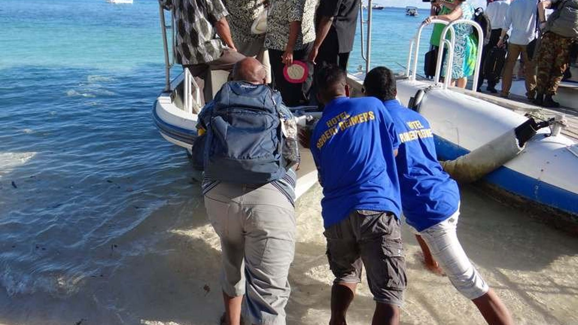 """Staff push a boat used to transport Pacific Islands Forum leaders from Eneko Island on September 5, 2013. A new Pacific regional pact calling for aggressive action to combat climate change has achieved a """"major accomplishment"""" by gaining US support, officials said Sunday."""