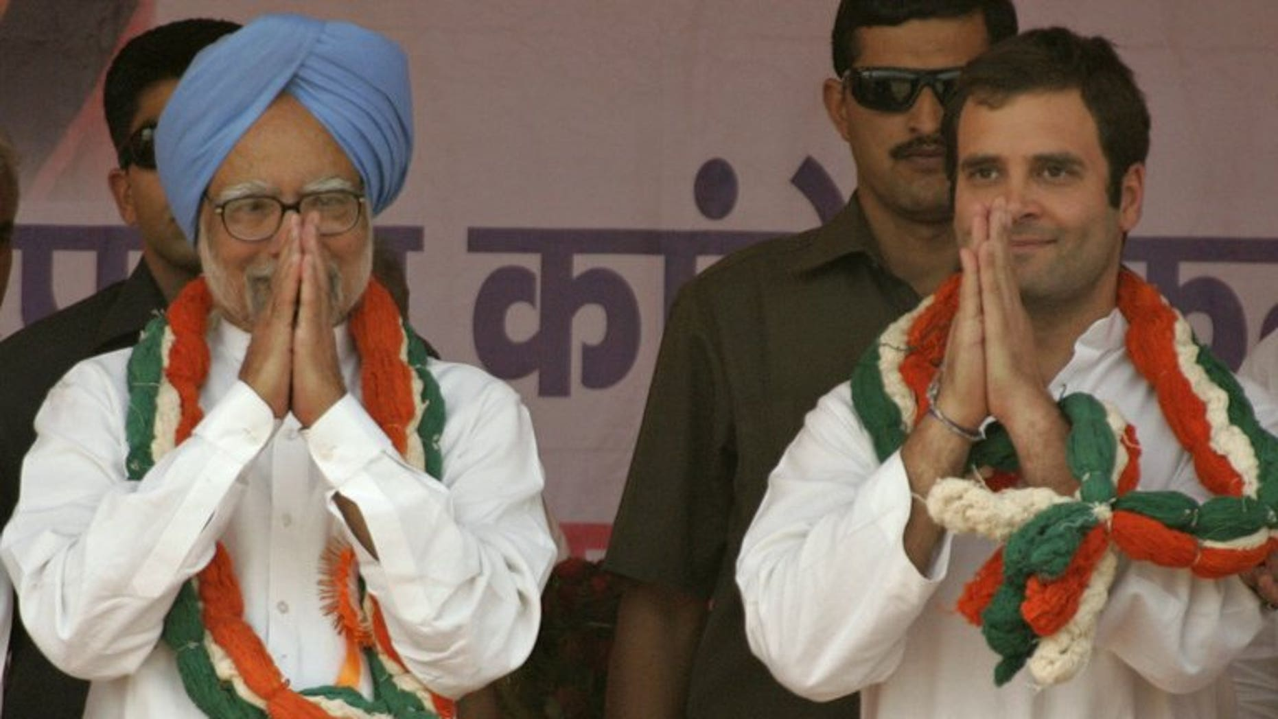 Indian Prime Minister Manmohan Singh (left) and Rahul Gandhi gesture to supporters during a rally in Banda, on April 30, 2011.