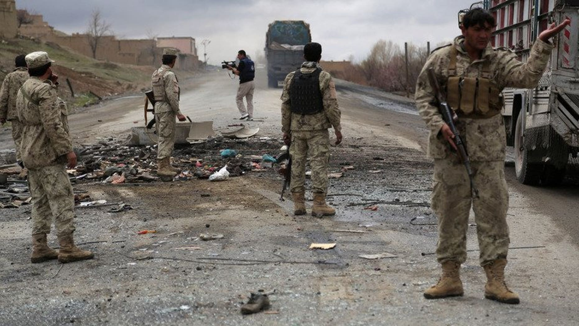 Afghanistan soldiers stand guard at the site of a roadside bomb blast in Saidabad district of Wardak province, on April 8, 2013. At least four Afghan intelligence agents were killed and dozens of civilians were wounded when a group of Taliban militants attacked an intelligence bureau in central Afghanistan.