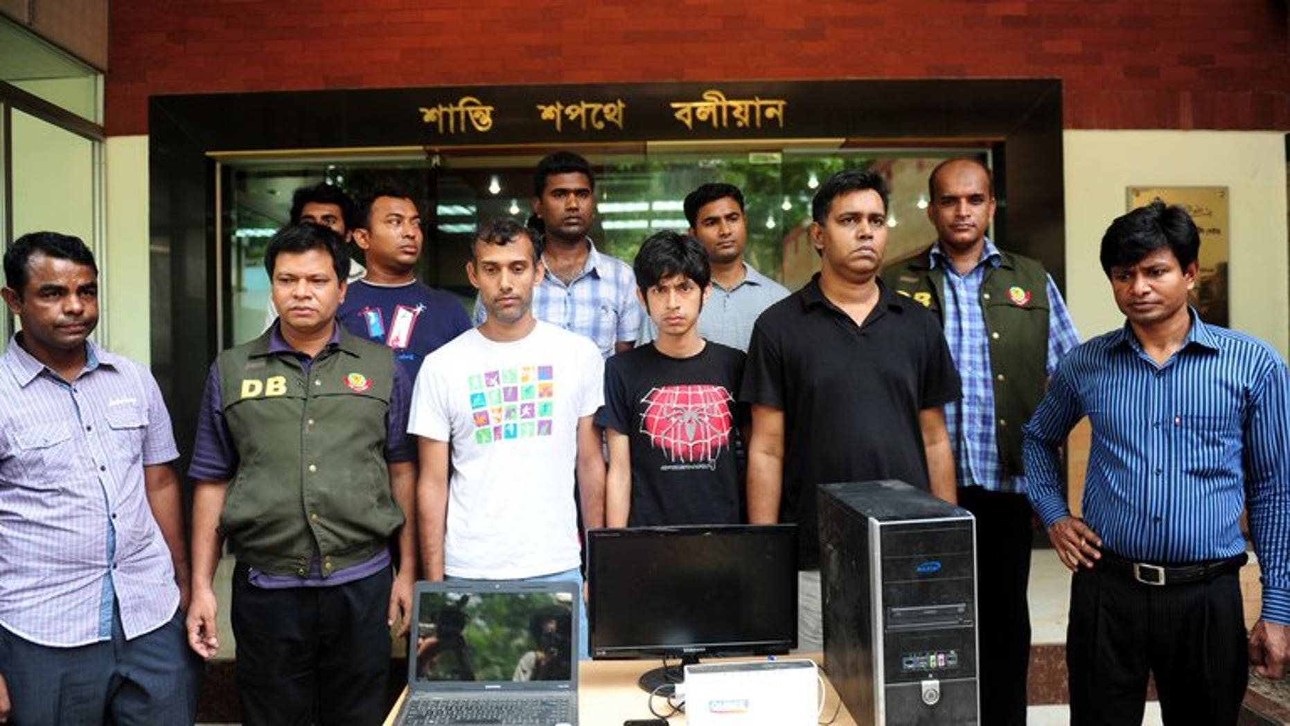 Bangladeshi police officials pose with three bloggers (C) during a press conference in Dhaka on April 2, 2013. Four Bangladeshi bloggers are facing up to seven years in jail after they were charged in court Sunday with defaming Islam and the Prophet Mohammed, a prosecutor told AFP.