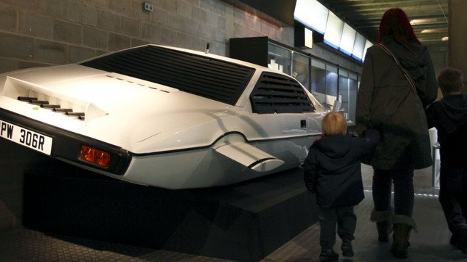 """A family walks past the Lotus Esprit underwater car from the James Bond film """"The Spy Who Loved Me"""" at the Beaulieu National Motor Museum on January 15, 2012."""