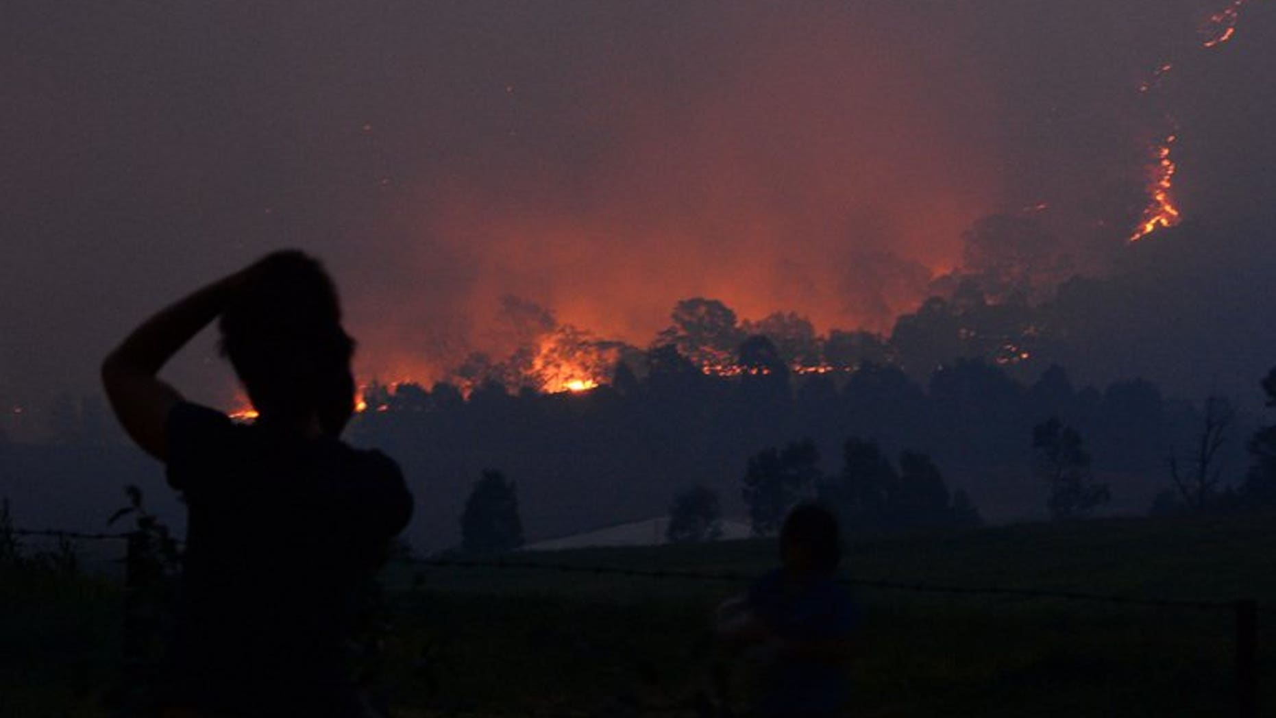 Residents look at the flames from a bush fire that erupted in Sydney's western suburb of Castlereagh, New South Wales on September 10, 2013. Dozens of bushfires erupted in Australia on Tuesday with six firefighters injured battling fierce infernos in western Sydney that destroyed two homes and which officials said could signal a difficult summer.