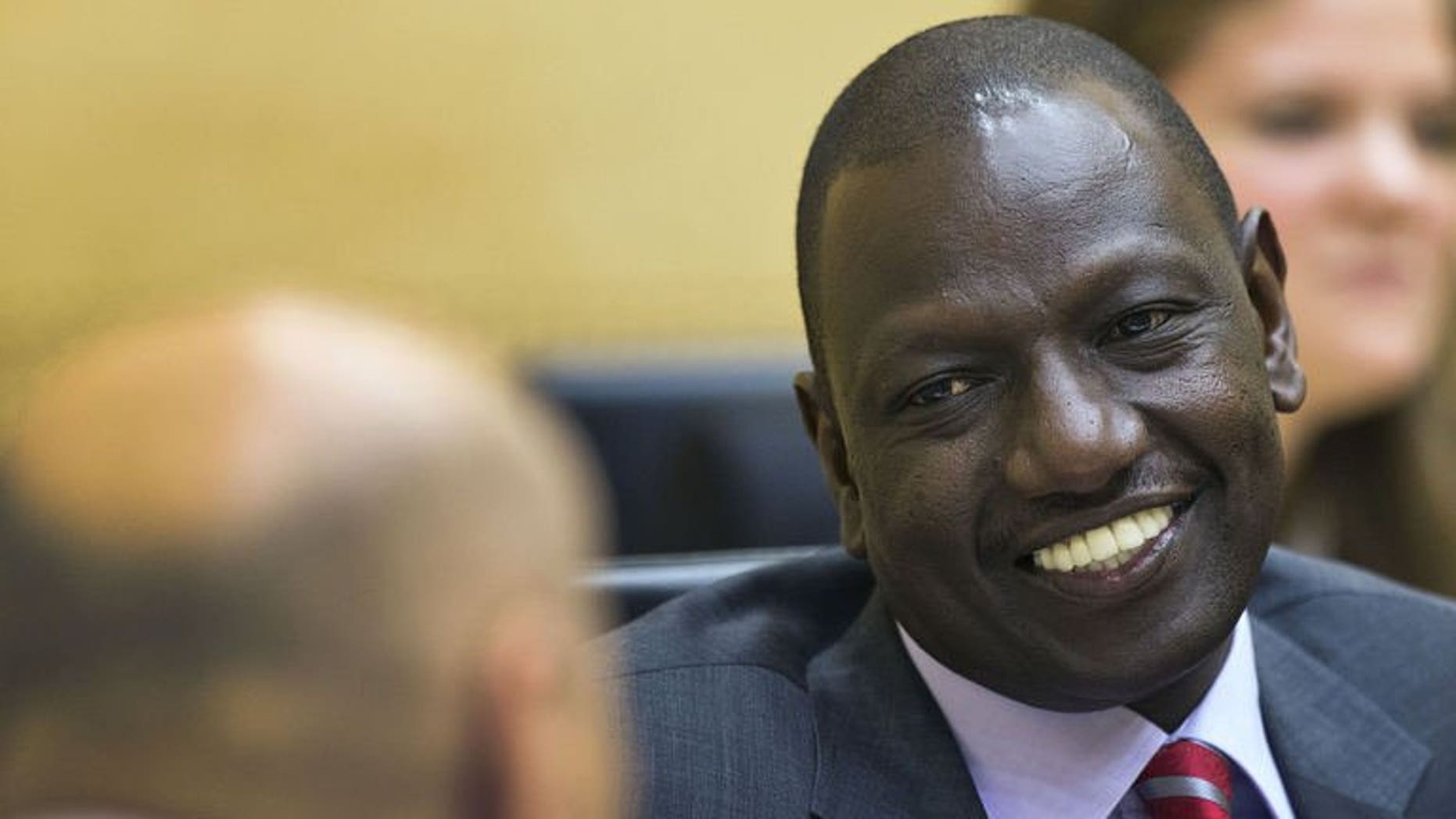 Kenya's Vice President William Ruto (right) speaks with his lawyer before the start of his trial at the International Criminal Court in The Hague, on September 10, 2013.