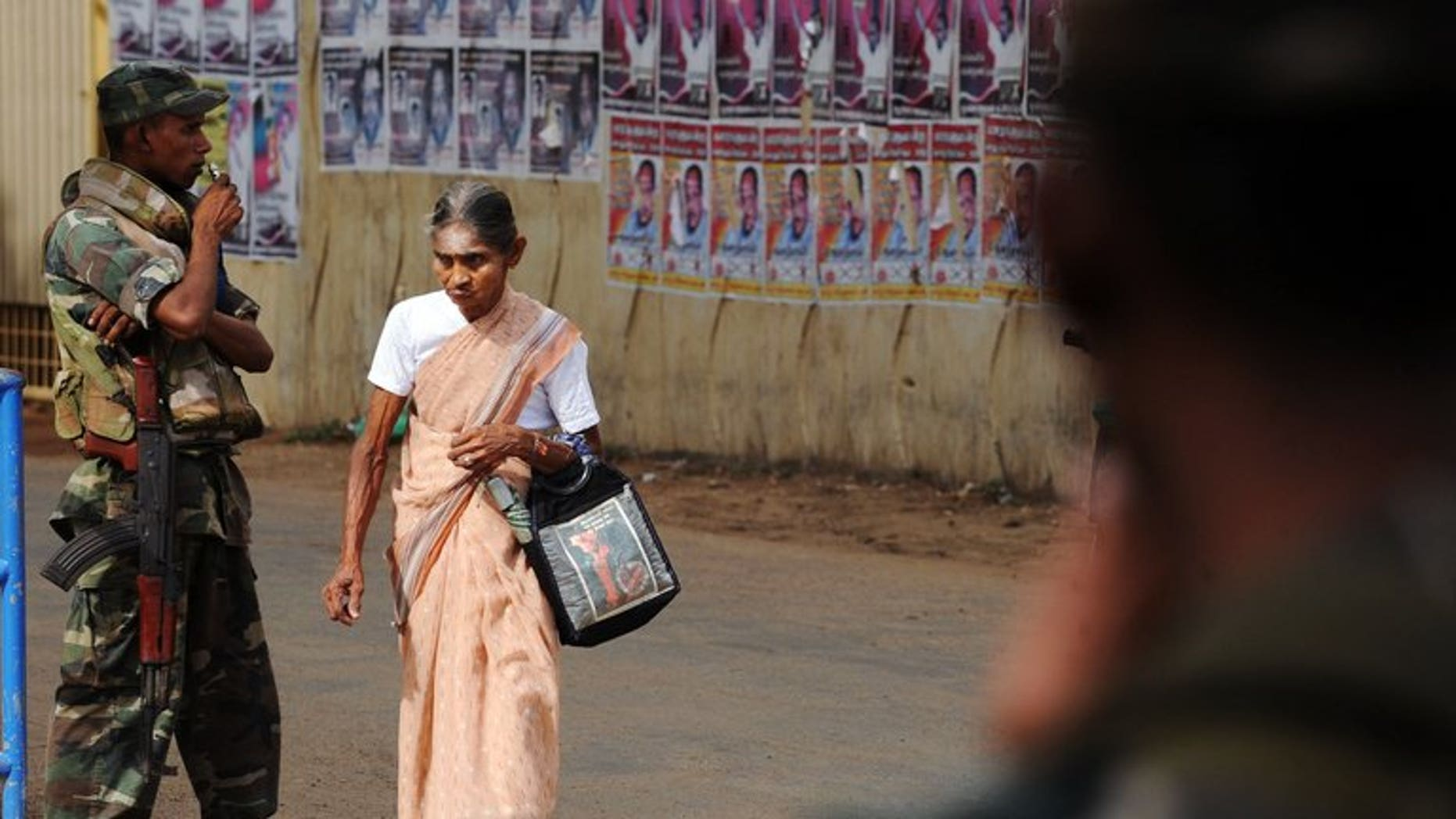An elderly Sri Lanka woman walks past armed soldiers in the northern town of Jaffna on April 30, 2010. Sri Lanka's main Tamil party Tuesday demanded troops be confined to barracks after accusing them of campaigning for the ruling party at key elections in the former separatist stronghold of Jaffna.