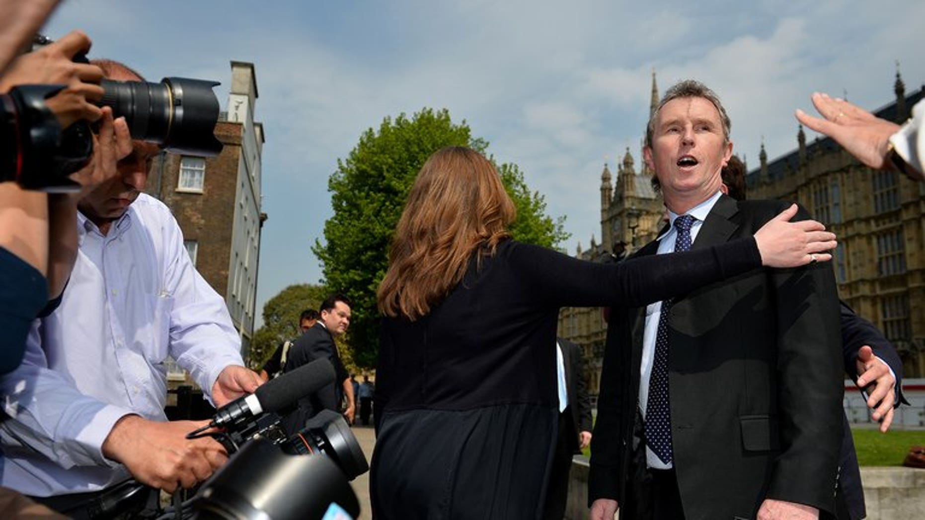 Journalists question deputy speaker Nigel Evans (R) outside London's Houses of Parliament, on May 7, 2013. Evans has been re-arrested on suspicion of indecent assault and sexually touching two further alleged victims, police said.