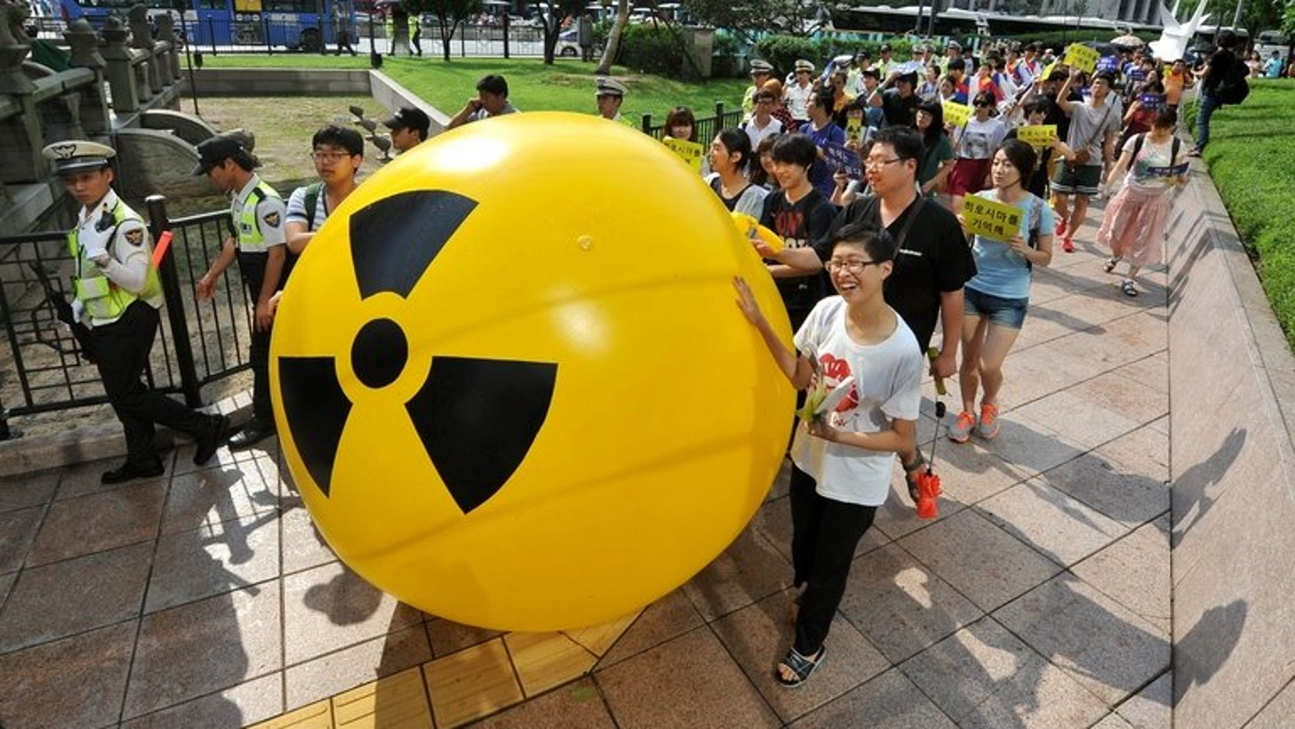 South Korean activists march while rolling a large balloon with a radioactivity warning sign during an anti-nuclear protest in Seoul on August 6, 2013. A former deputy minister has been charged with taking bribes as part of a corruption probe into South Korea's nuclear industry which has already indicted nearly 100 people, prosecutors said Tuesday.