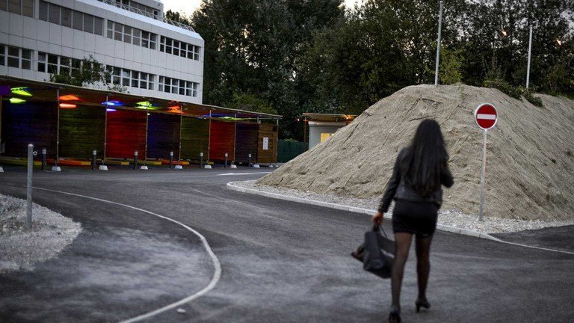 "A prostitute walks past so-called ""sex boxes"" at the opening day of Switzerland's first sex drive-in on August 26, 2013 in Zurich. The Swiss parliament voted Tuesday to raise the legal prostitution age from 16 to 18, tightening the country's liberal sex-trade laws to bring them in line with European standards."