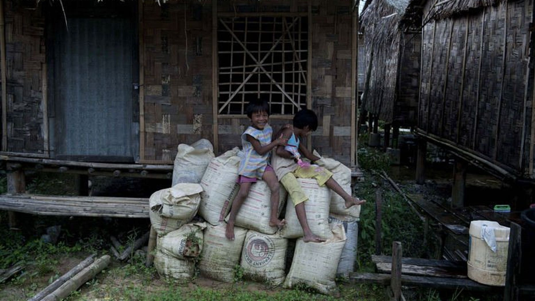Children sit outside their bamboo house built in the compound of a Buddhist monastery and meditation center sheltering hundreds of displaced families in a suburb of Myanmar's former capital Yangon on July 19, 2013.
