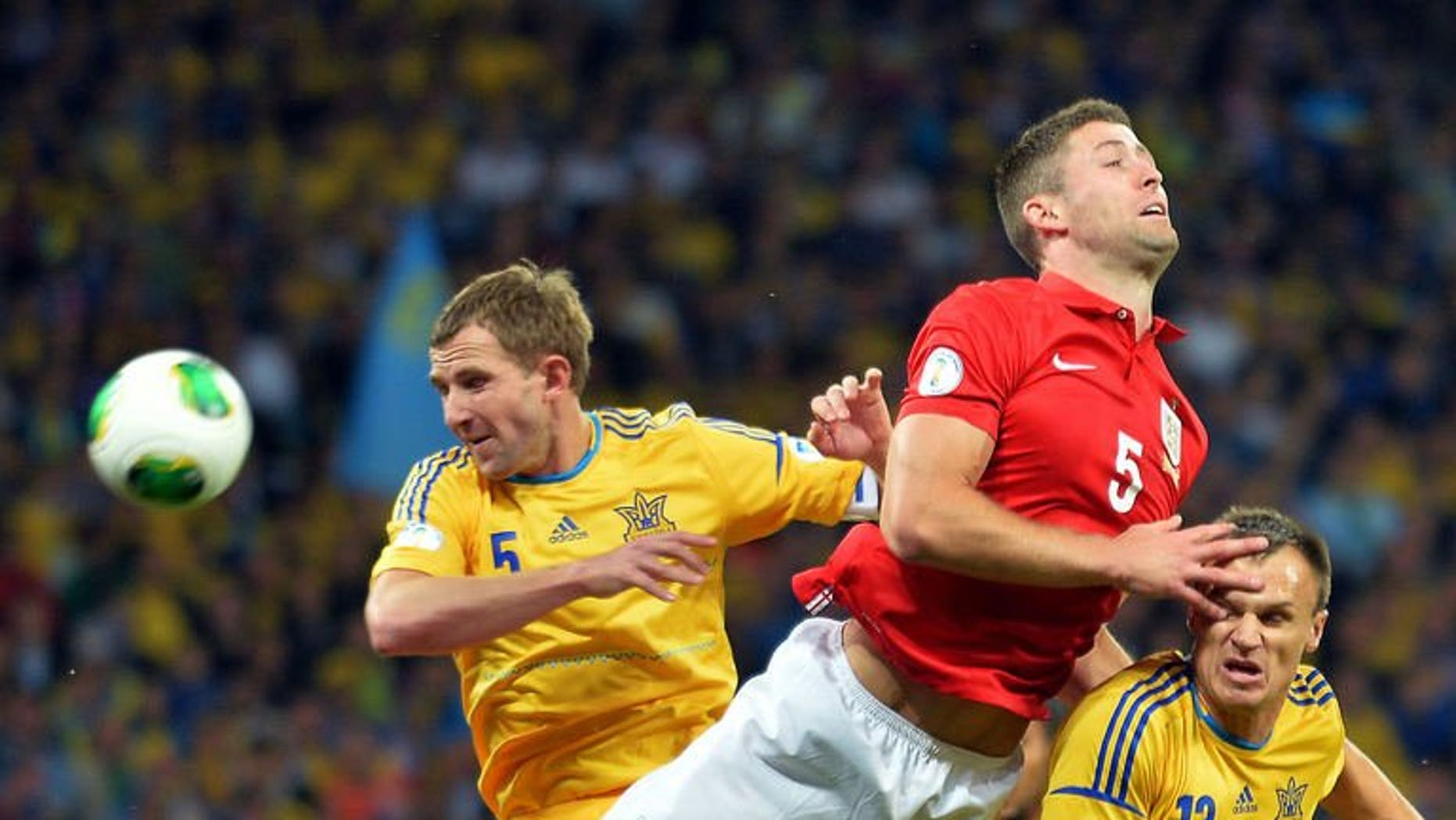 England's defender Gary Cahill (C) challenges Ukraine's defenders Olexandr Kucher (L) and Vyacheslav Shevchuk (R) during the 2014 FIFA World Cup European zone group H football match in Kiev on September 10, 2013. The match ended 0-0.