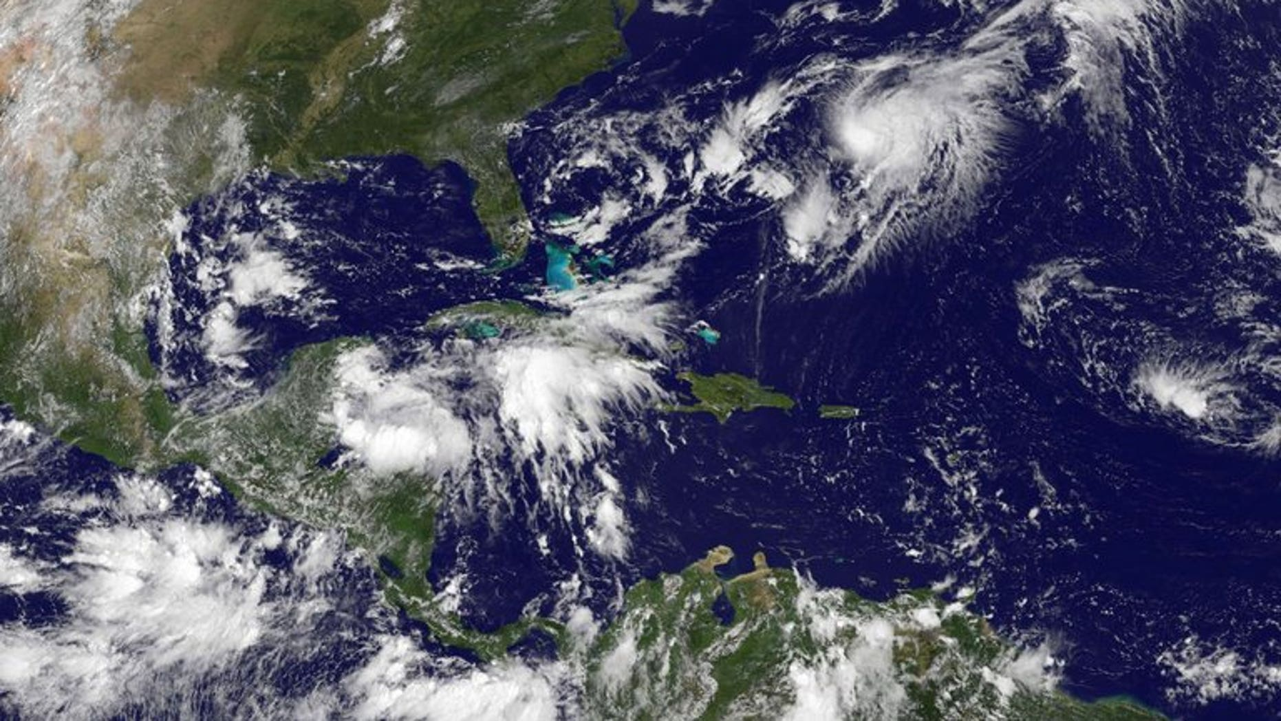 This NASA satellite image, released September 2013, shows Tropical Storm Gabrielle (Upper R) closing in on Bermuda. Forecasters said the storm, which was some 120 miles south of the island, was strengthening and approaching.