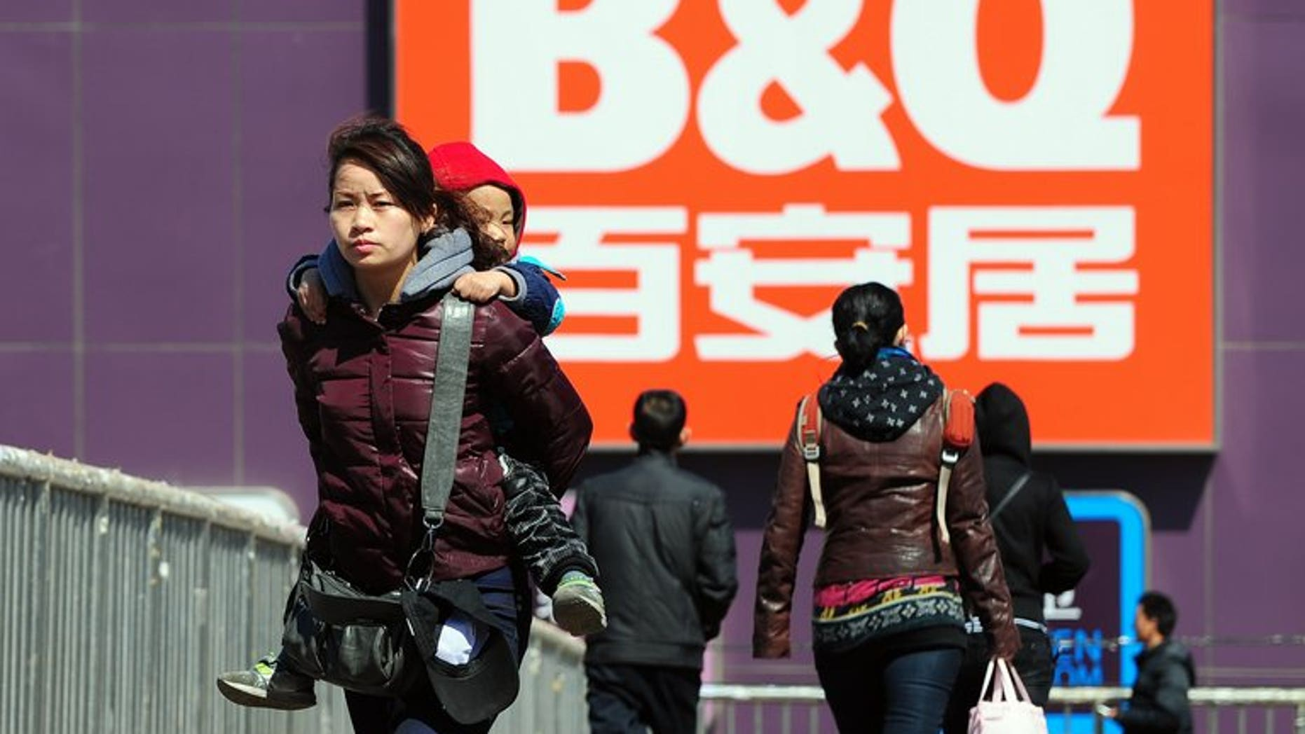 A woman carries a child on her back as pedestrians cross a footbridge overpass in front of a B&Q DIY shop in Beijing on March 24, 2011. Kingfisher, Europe's biggest home-improvements retailer, said that group net profit surged by 70 percent during the first half of its financial year mainly thanks to an exceptional tax gain.