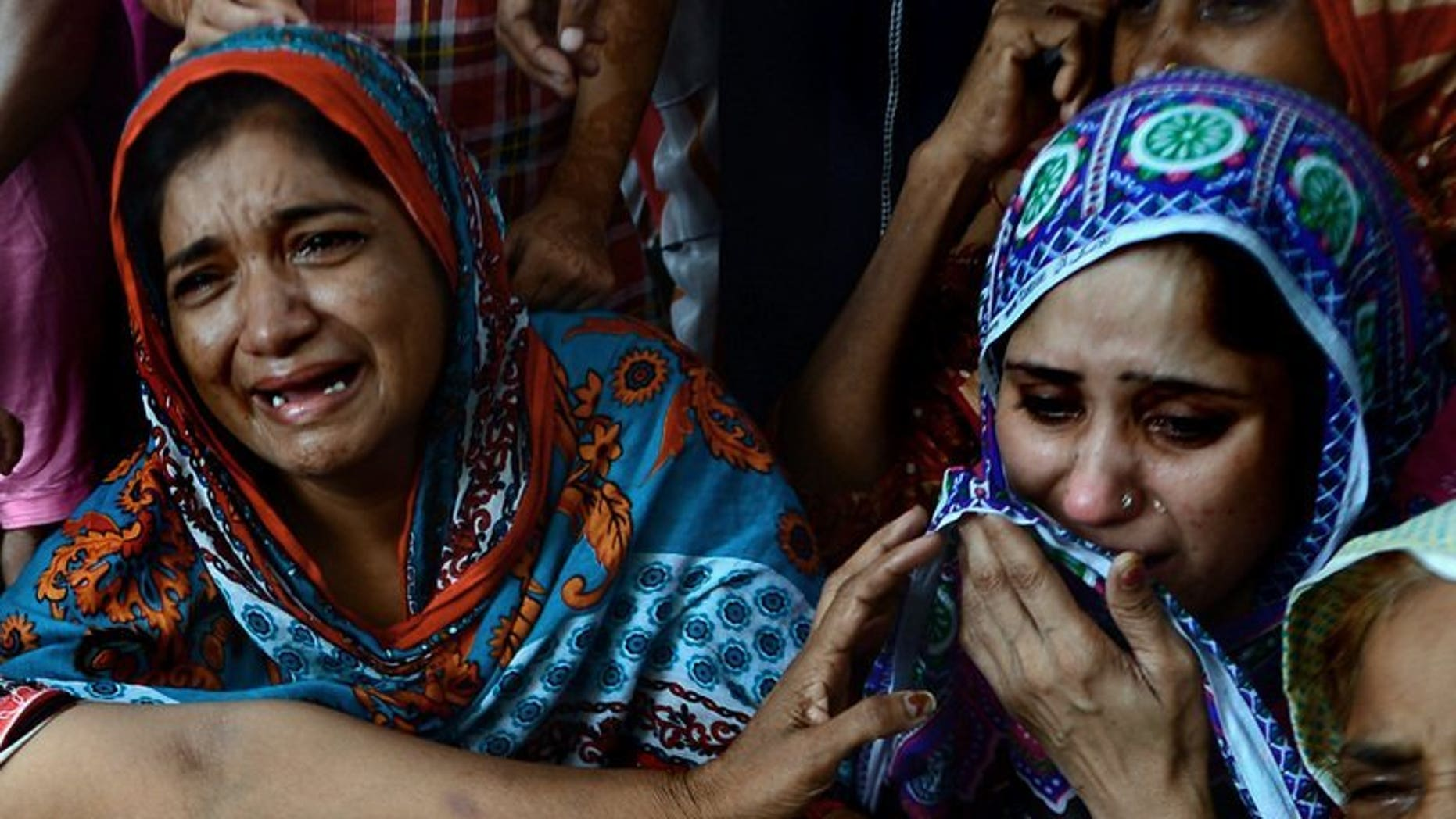 Pakistani women mourn the death of a relative who was killed after drinking toxic liquor in Karachi, on August 11, 2013. Toxic liquor has killed at least 12 people in central Pakistan, according to police and health officials.
