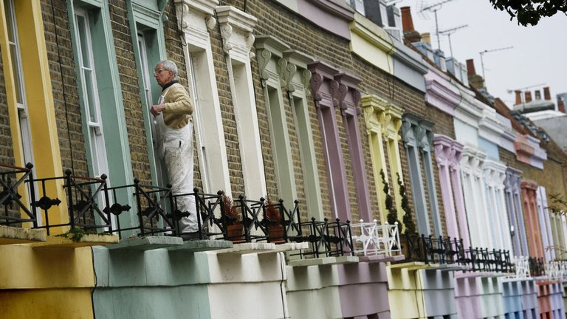 """A decorator paints a window frame on a house in Camden in London, on November 3, 2008. The United Nations' special rapporteur on housing called for Britain to scrap its so-called """"bedroom tax"""" because of its """"shocking"""" impact on the poor and vulnerable, sparking an angry response from the government."""