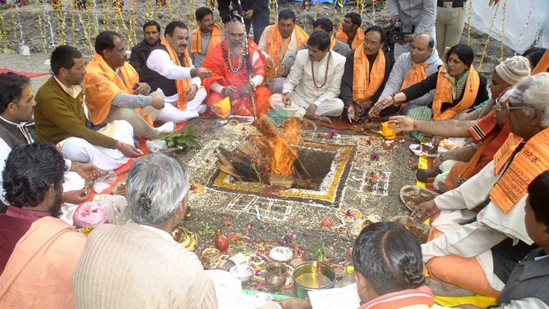 Indian Hindu devotees sit around a fire as they give offerings during prayers at Kedarnath temple in Uttarakhand state, on September 11, 2013. A Hindu temple at the centre of a devastated area of the Indian Himalayas hit by floods in June, has reopened for prayers as reconstruction efforts continued across the region.