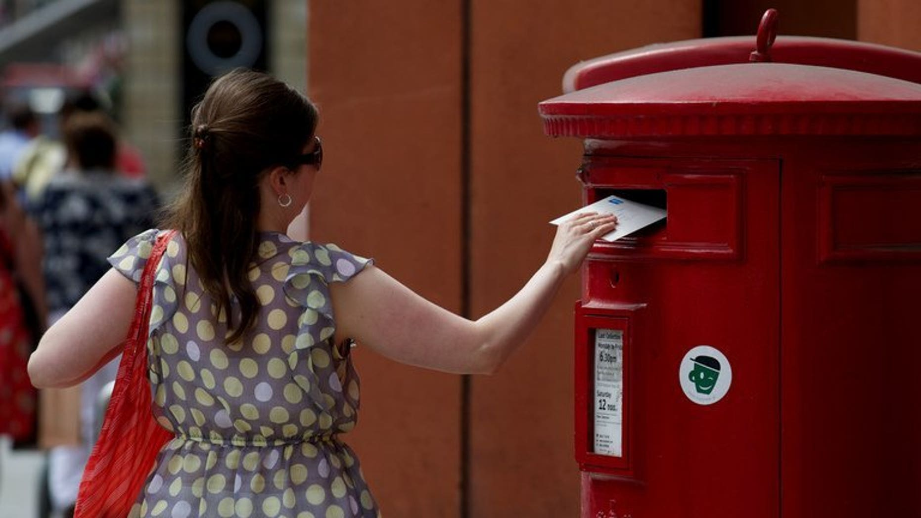A woman posts a letter in a Royal Mail post box in London on July 10, 2013. Britain's government announced plans to privatise more than half of Royal Mail, the state-run postal delivery service, following a major restructuring in recent years triggered by a surge in email use.