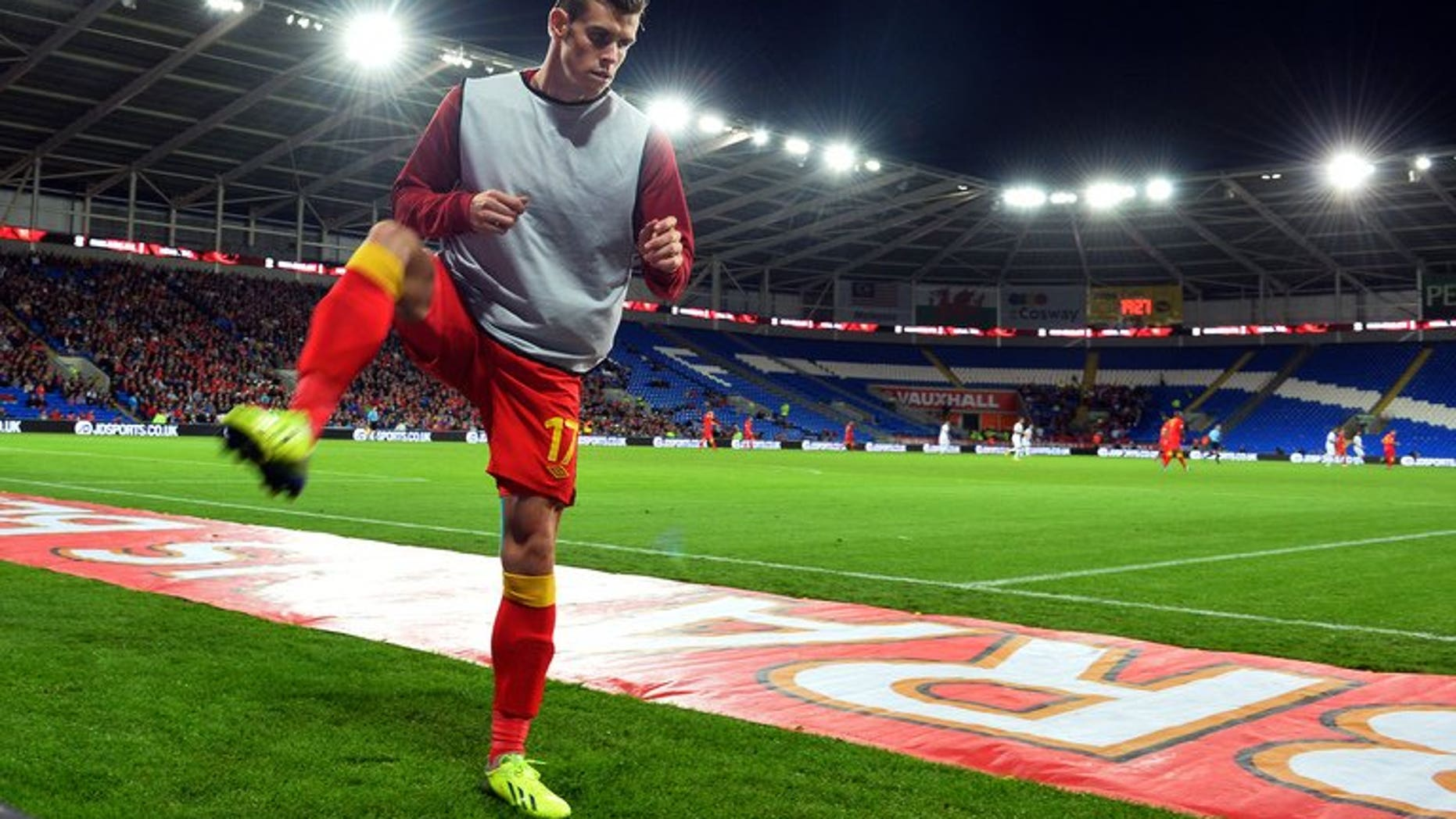 """Wales midfielder Gareth Bale warms up during the World Cup 2014 European Zone group A qualifying football match between Wales and Serbia at Cardiff City Stadium on September 10, 2013. Gareth Bale said on Thursday he was """"a bit behind"""" his new Real Madrid team-mates in terms of fitness, after a close season hampered by injury."""