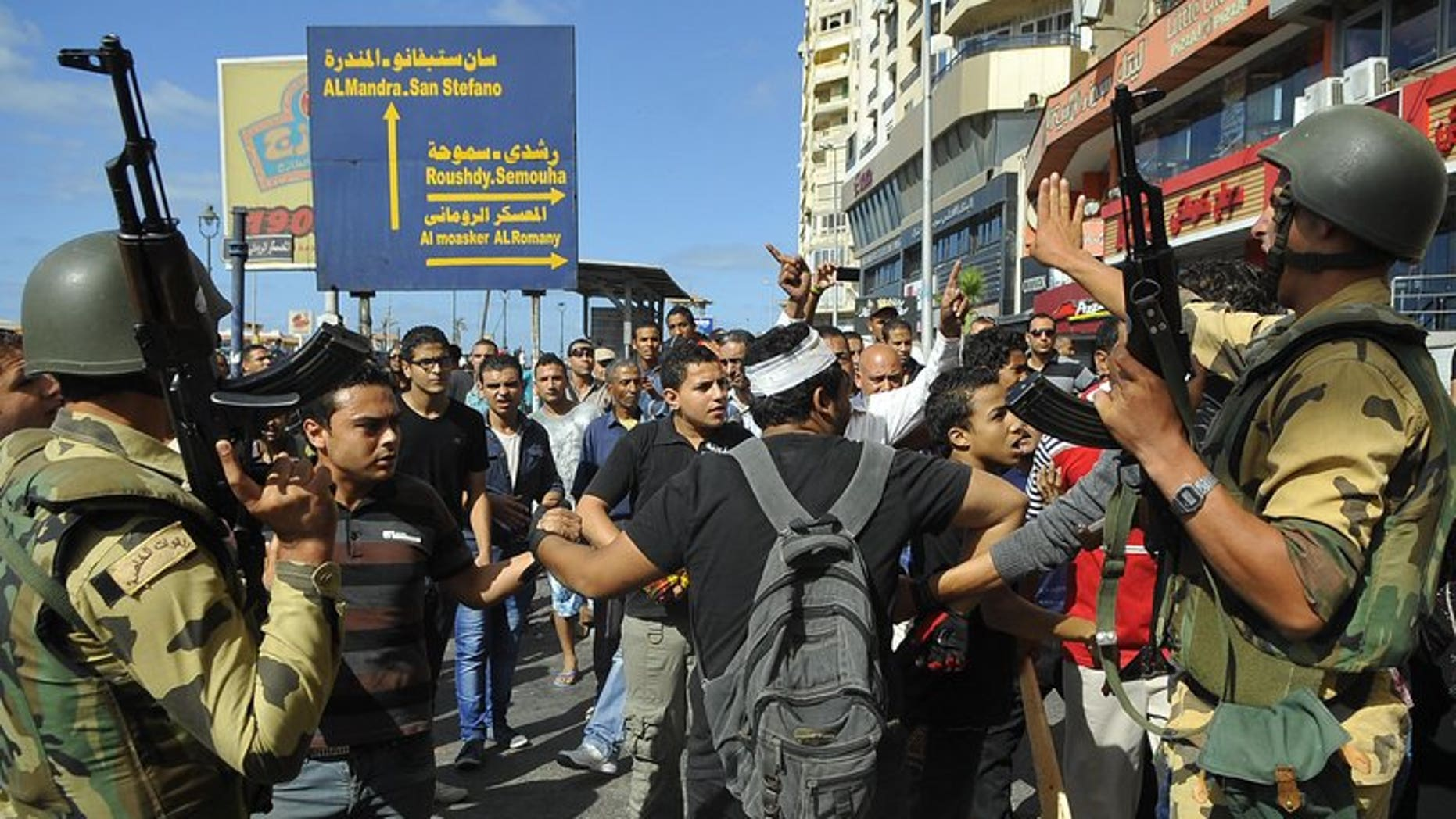 Egyptian soldiers patrol as supporters of the Muslim Brotherhood and Egypt's ousted president Mohamed Morsi clash with opposition demonstrators in Alexandria on September 6, 2013. Interim president Adly Mansour on Thursday extended by two months Egypt's state of emergency in force since mid-August, his spokesman said.