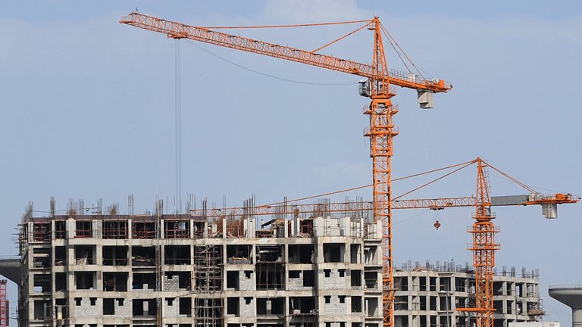 Construction cranes stand at an under construction building on the outskirts of Islamabad on April 15, 2009. The International Monetary Fund warned Pakistan that economic growth could be worse than expected next year due to strict austerity measures built into a $6.7 billion rescue loan.