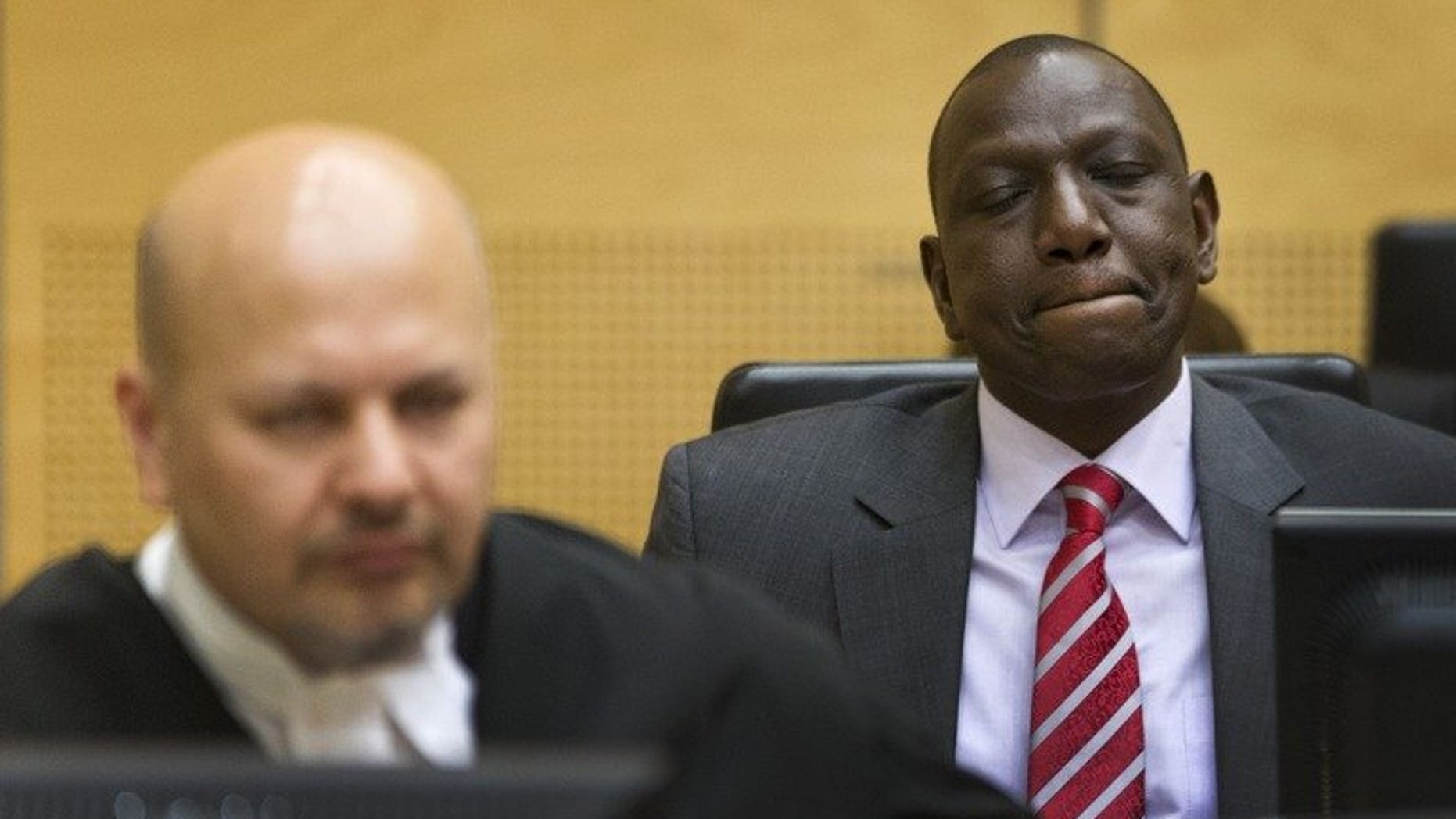 "Kenya's Deputy President William Ruto (right) reacts as he sits in the courtroom before their trial at the International Criminal Court (ICC) in The Hague on September 10, 2013. Kenyatta has been ""distressed"" by the start of an international trial of his deputy for crimes against humanity,"