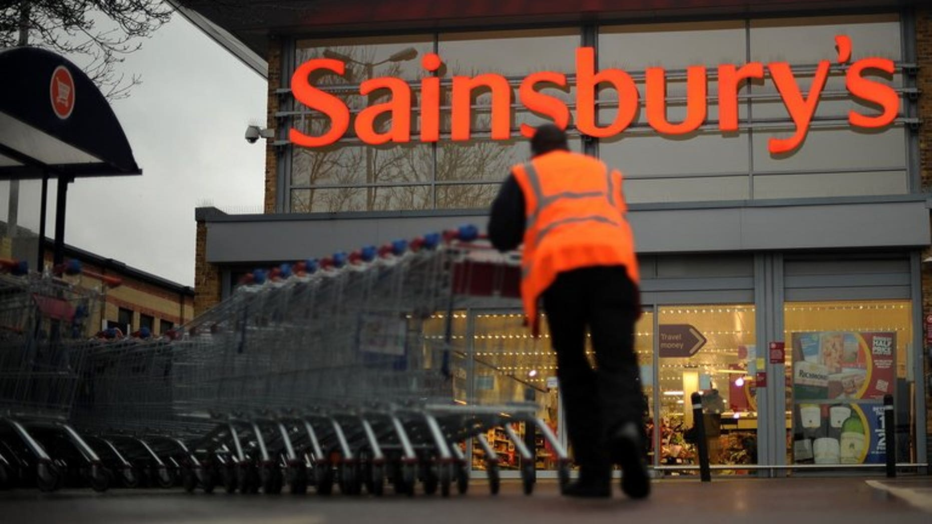 An employee moves shopping trolleys in front of a Sainsbury's store in London, on January 12, 2011. Sainsbury's has issued a recall of all of its bagged watercress and salads containing watercress due to an outbreak of E. coli.