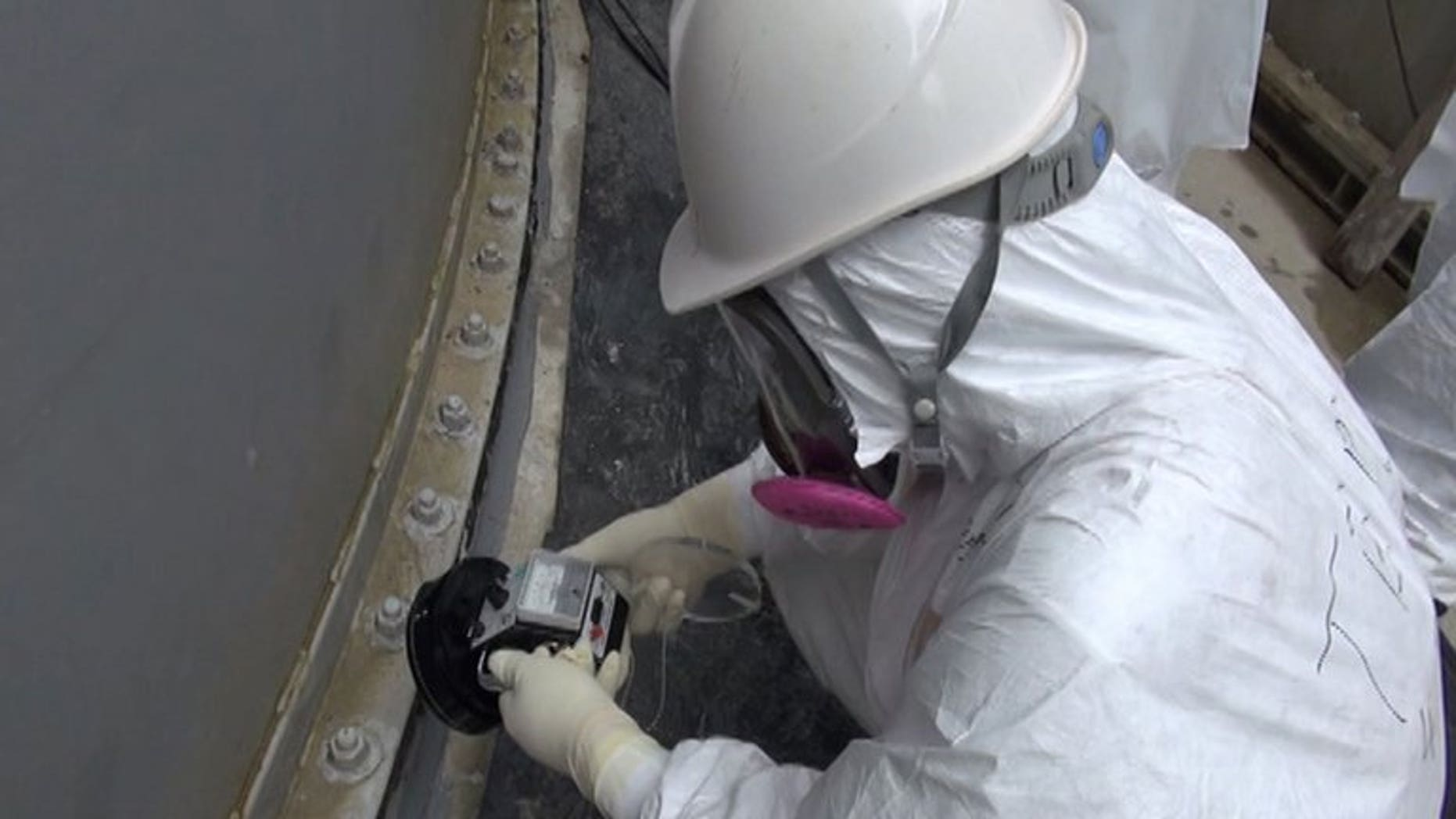 Image taken by TEPCO on September 4, 2013 shows a worker checking radiation levels at a water tank at the Fukushima nuclear power plant. Vapour has begun rising again from a reactor at the plant, more than two-and-a-half years after its core melted down, TEPCO said Friday.