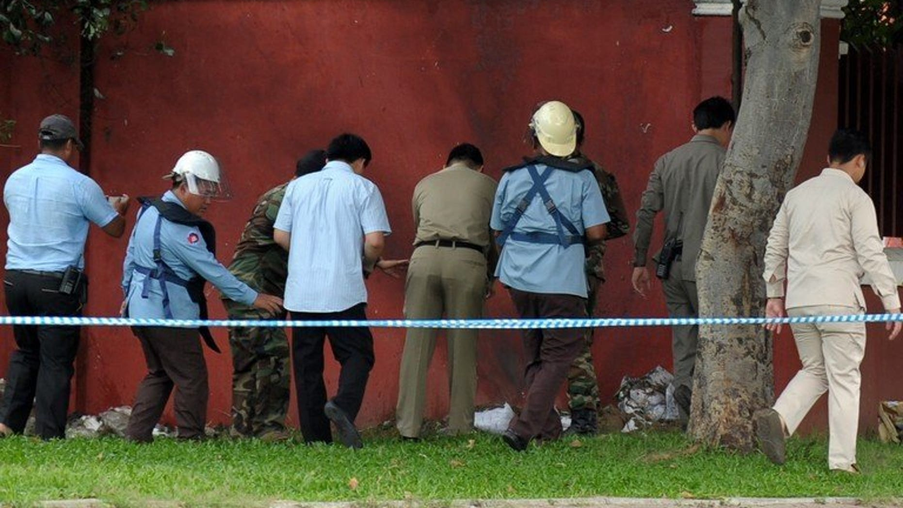 Bomb officials and police inspect a home-made bomb near Cambodia's parliament in Phnom Penh on September 13, 2013. The makeshift bomb was safely detonated by explosive experts, causing a loud bang that shook some nearby buildings, police said.