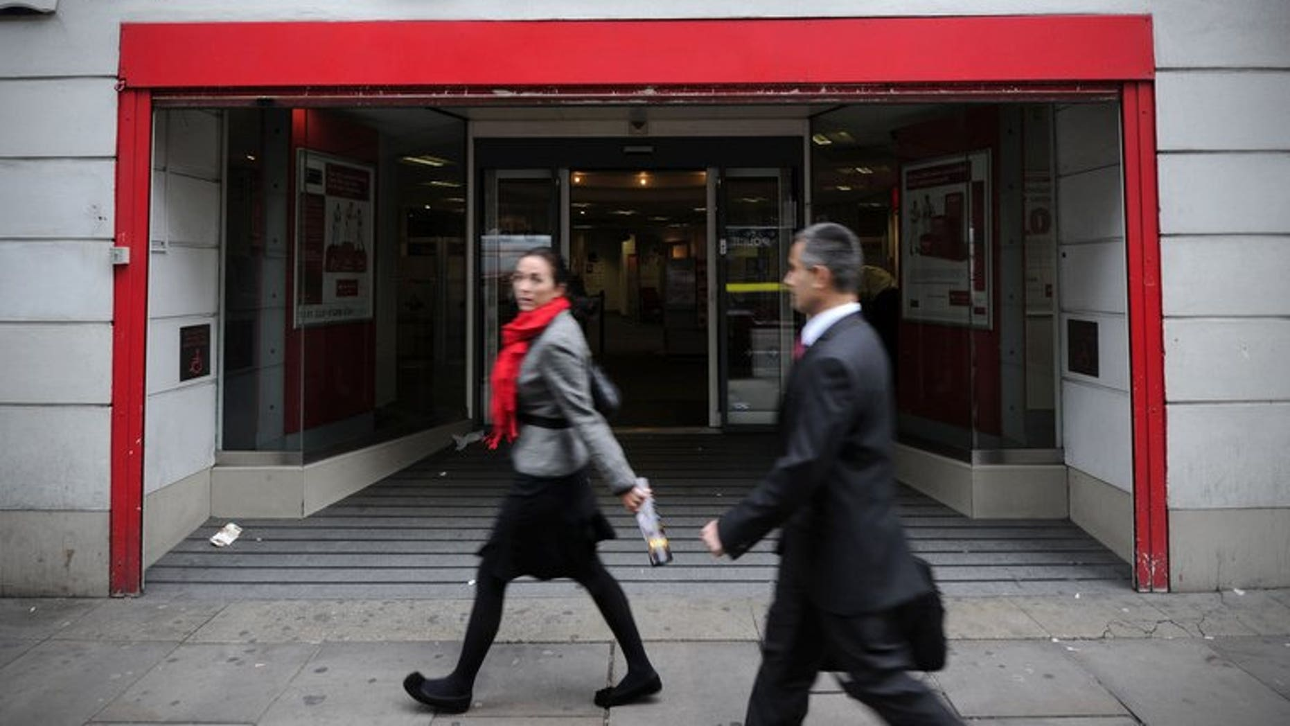 "People walk past a branch of Santander in central London, on October 7, 2011. British police said Friday they have arrested 12 men over a ""sophisticated"" plot to remotely take control of a computer at a branch of Santander bank and steal millions of pounds."