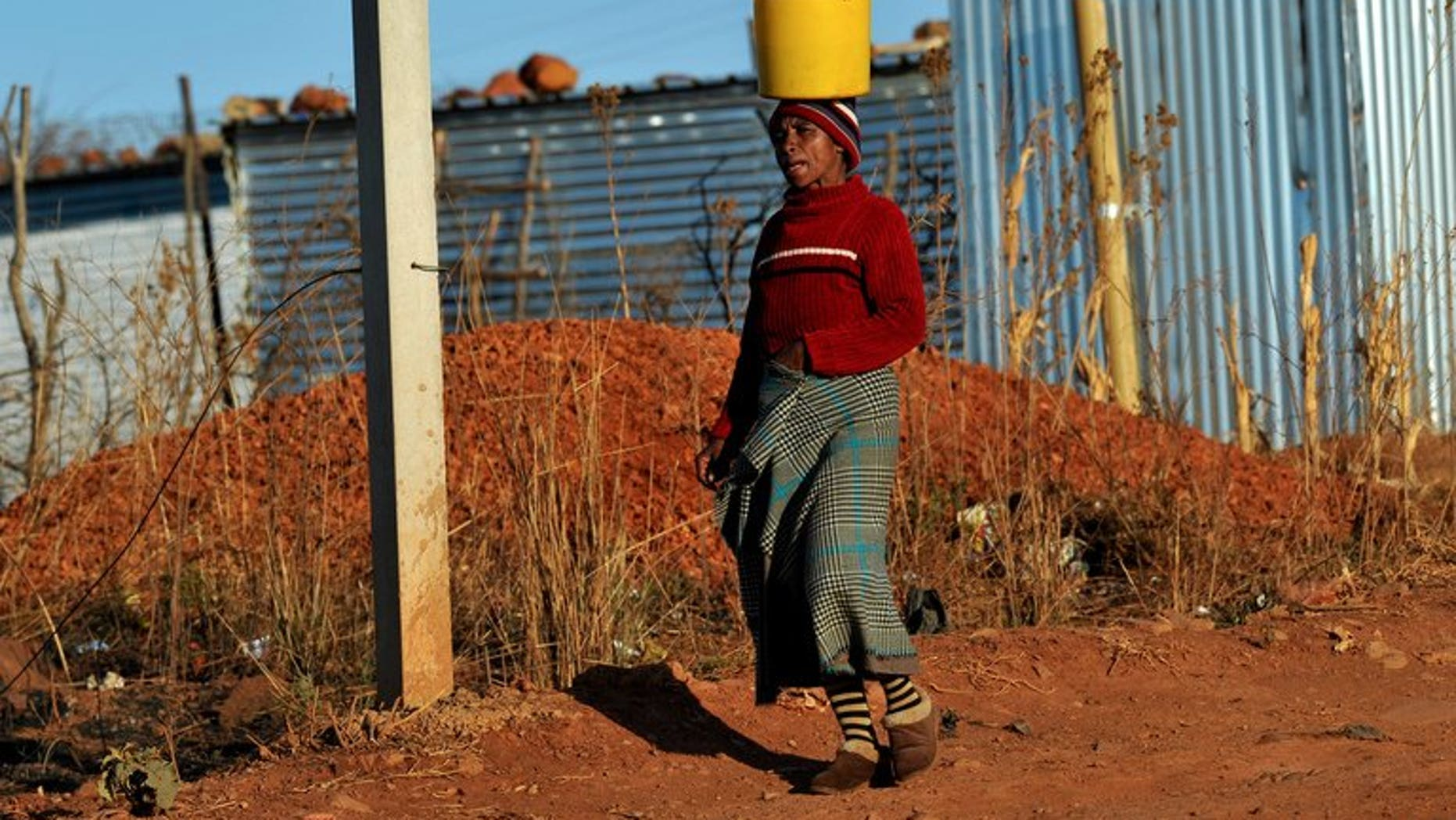 A woman brings water to her shack as workers who support the National Union of Mineworkers start a strike in Carletonville on September 3, 2013. South African construction workers have ended a three week strike after reaching a 12 percent wage hike deal with employers, their union said on Friday.