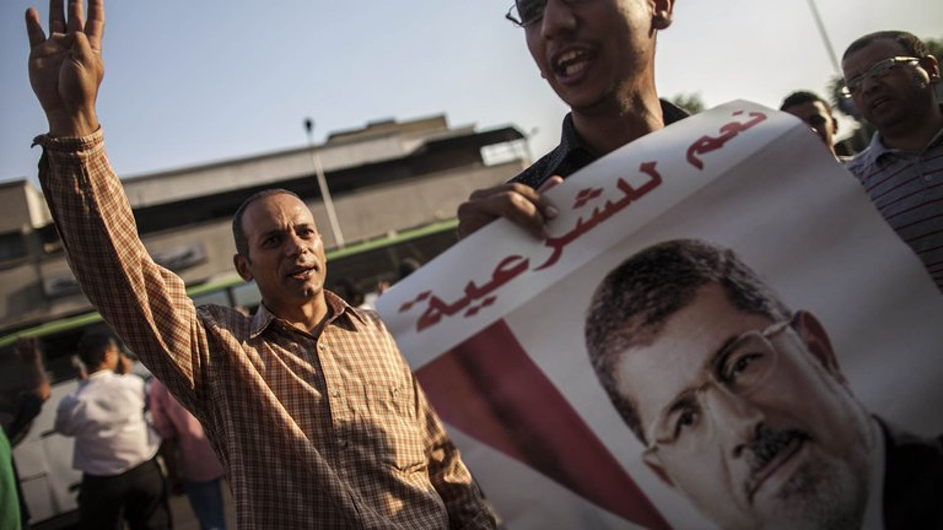 Muslim Brotherhood members and supporters of ousted president Mohammed Morsi show his portrait during a demonstration against the army-installed government on September 10, 2013 in Cairo. Morsi supporters rallied in Cairo after Friday prayers chanting angry slogans against the military, with clashes reported elsewhere in Egypt.