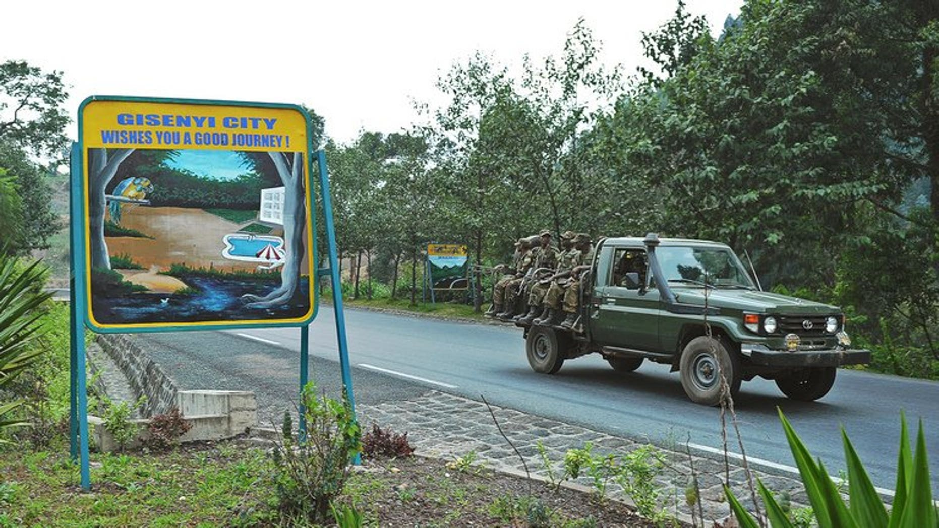 Rwandan soldiers pass a sign welcoming drivers to the city of Gisenyi, on the border with the Democratic Republic of Congo on August 30, 2013. Southern African nations have expressed concern at the growing number of Rwandan troops on the border of the Democratic Republic of Congo and said it hoped an invasion was not imminent.