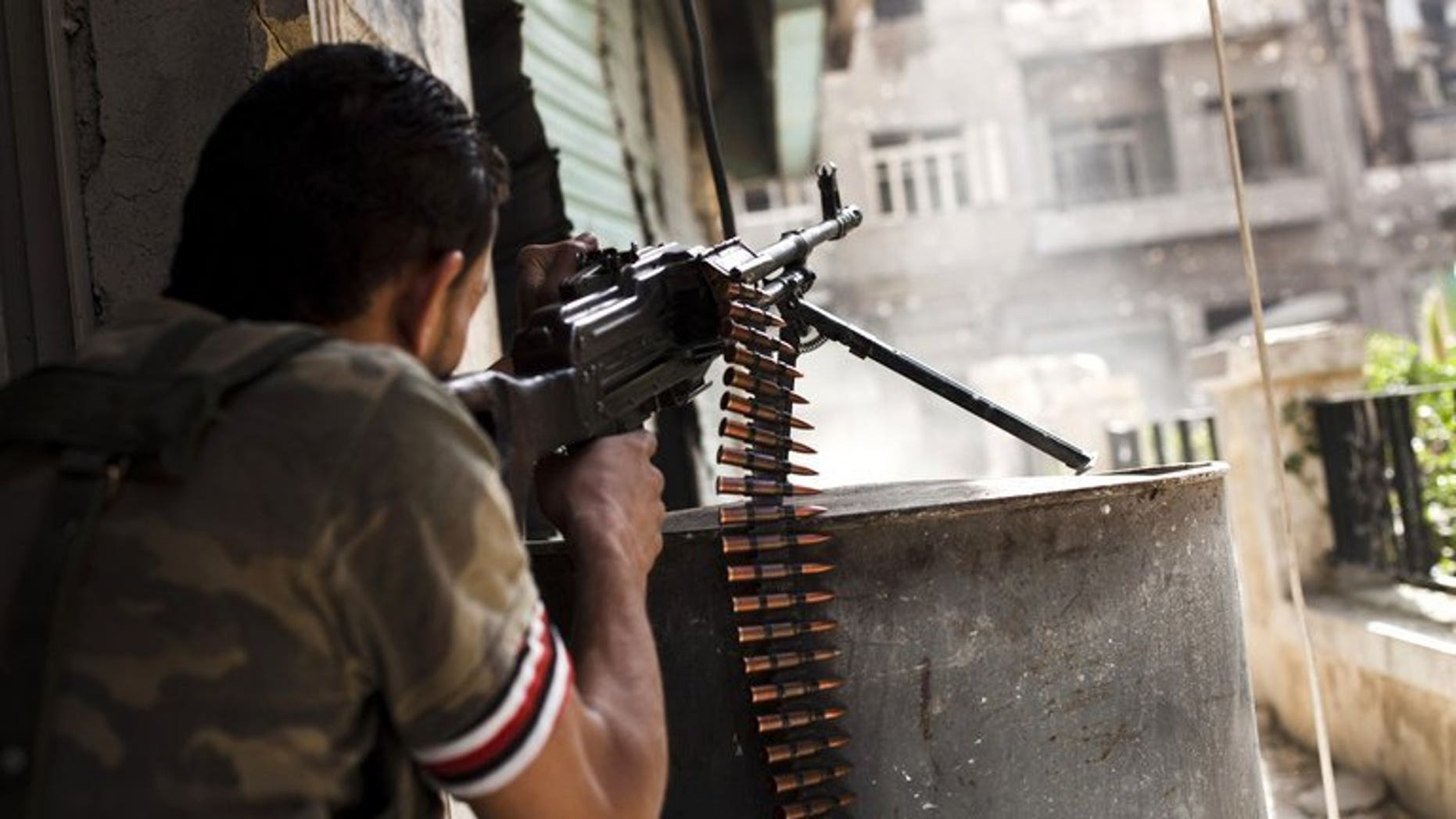 """A Syrian rebel fighter fires his gun against a government troop position in the northern city of Aleppo, on October 21, 2012. British Foreign Secretary William Hague has welcomed a US-Russian deal to eliminate Syria's chemical weapons and said the priority now was the """"full and prompt implementation"""" of the agreement."""