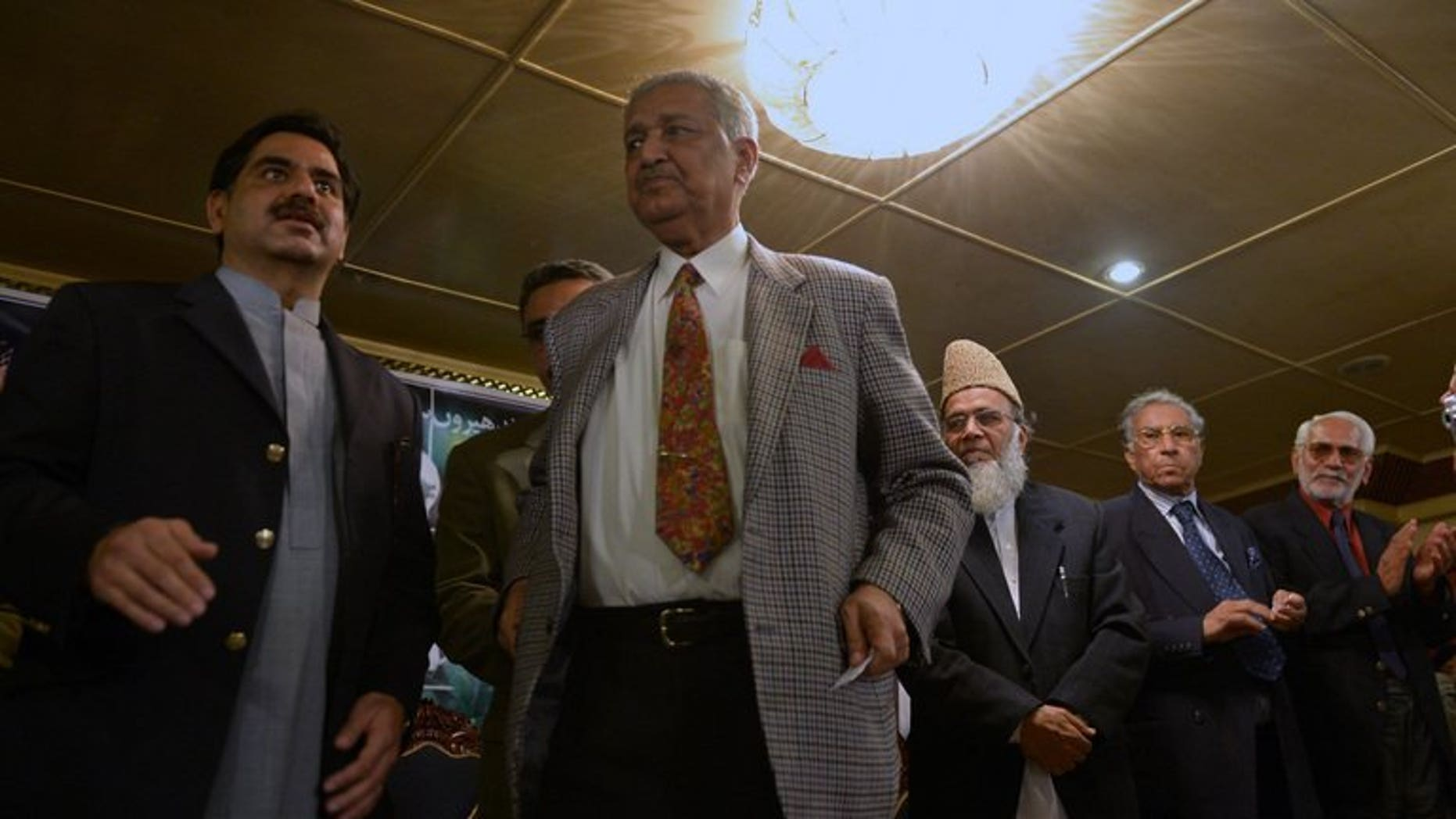 Former Pakistani nuclear scientist and chairman of Tehreek-e-Tahafuz Pakistan party, Abdul Qadeer Khan (2L), stands to give a speech during a public meeting in Islamabad on February 26, 2013.