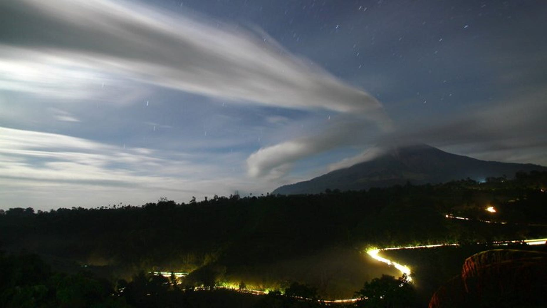File picture shows plume of volcanic ash being emitted by Mount Sinabung in Tanah Karo district in North Sumatra province, seen under moon light from in this time exposure taken late September 16, 2010.