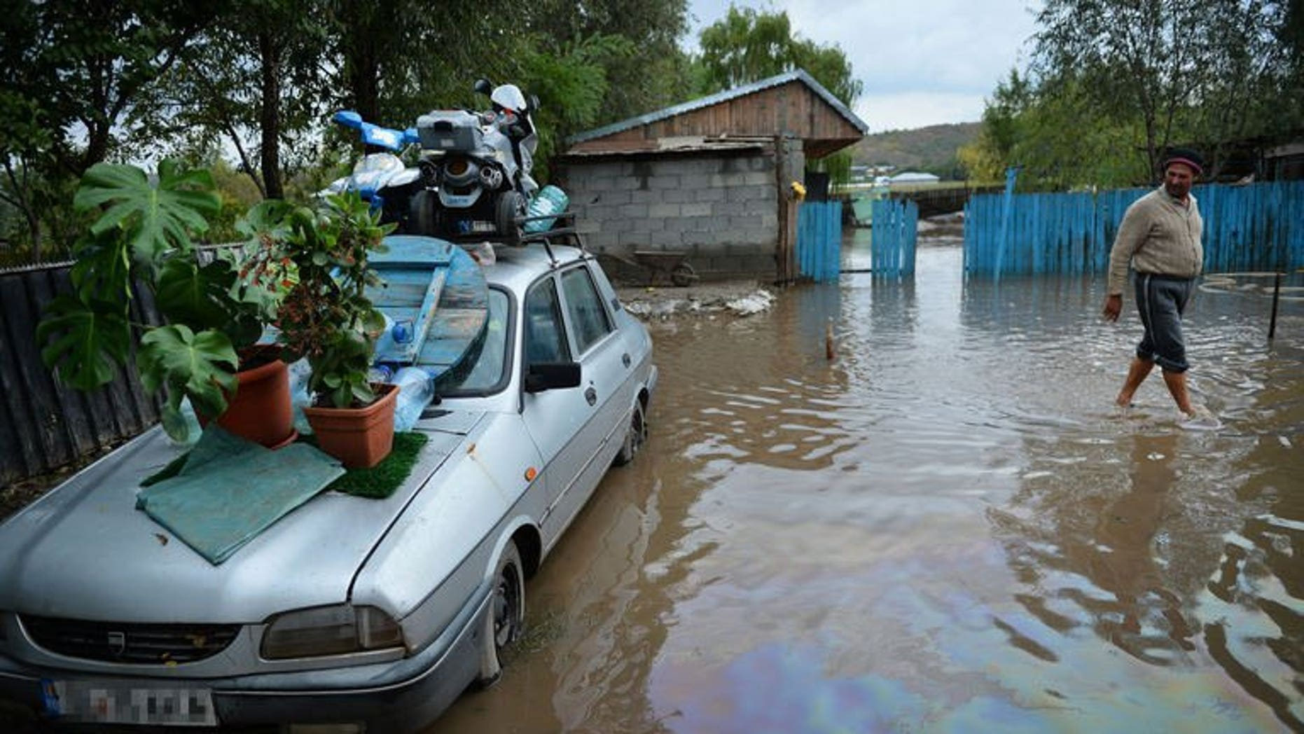 A man walks through flooded courtyard in Slobozia Conachi, eastern Romania on September 14, 2013. Flash floods have killed nine people and forced thousands to flee their homes in eastern Romania in the last four days, the authorities said Sunday.