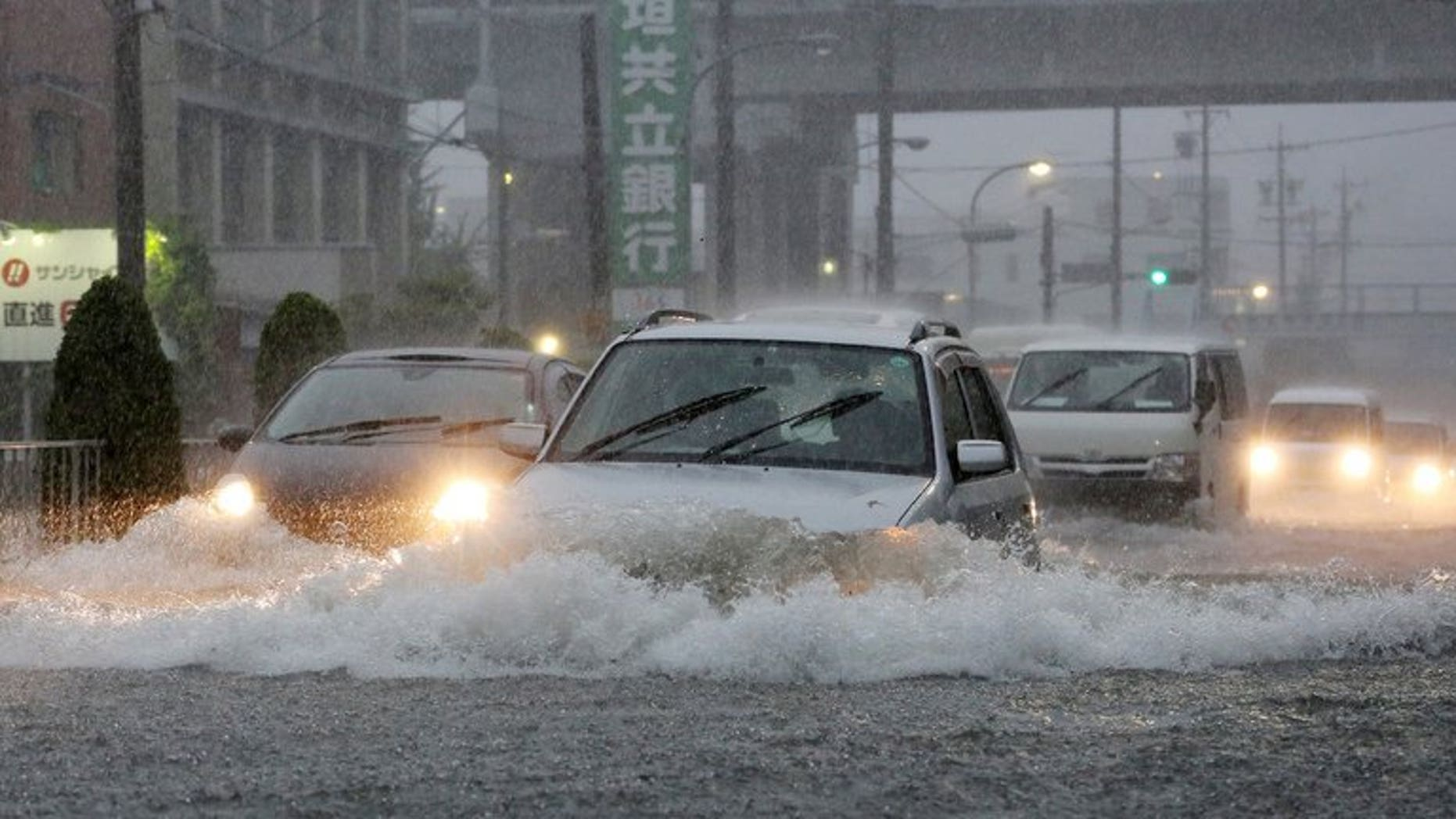 Cars manouever through flood waters on a road in Nagoya, Aichi prefecture on September 4, 2013.