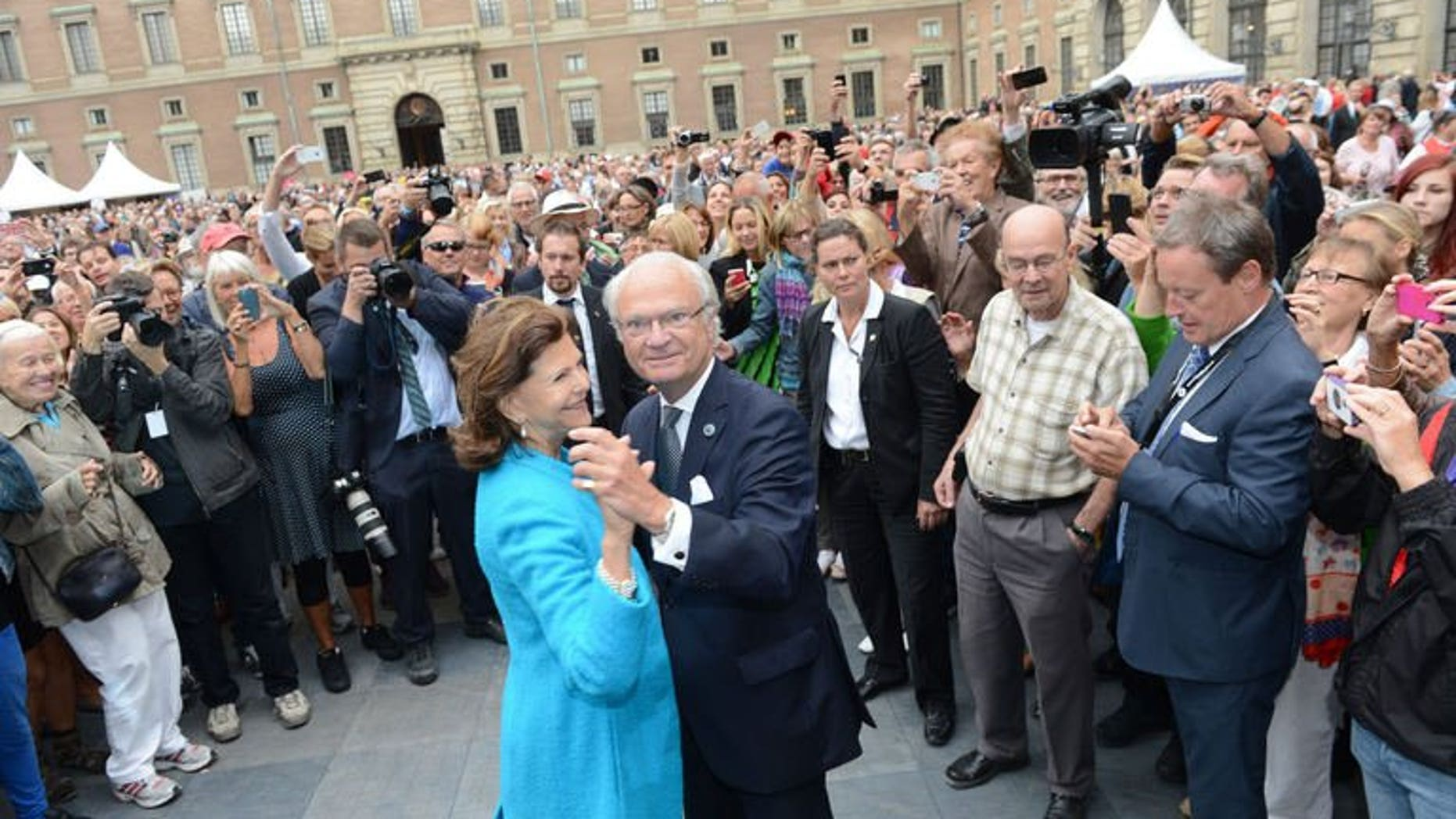 Queen Silvia and King Carl Gustaf of Sweden lead a dance in the palace courtyard in Stockholm on September 15, 2013.