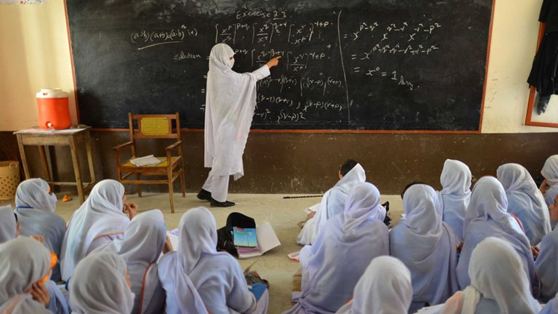 This photograph taken on June 21, 2013 shows a Pakistani teacher leading a class of girls at a school in Mingora, the main town of Swat valley.