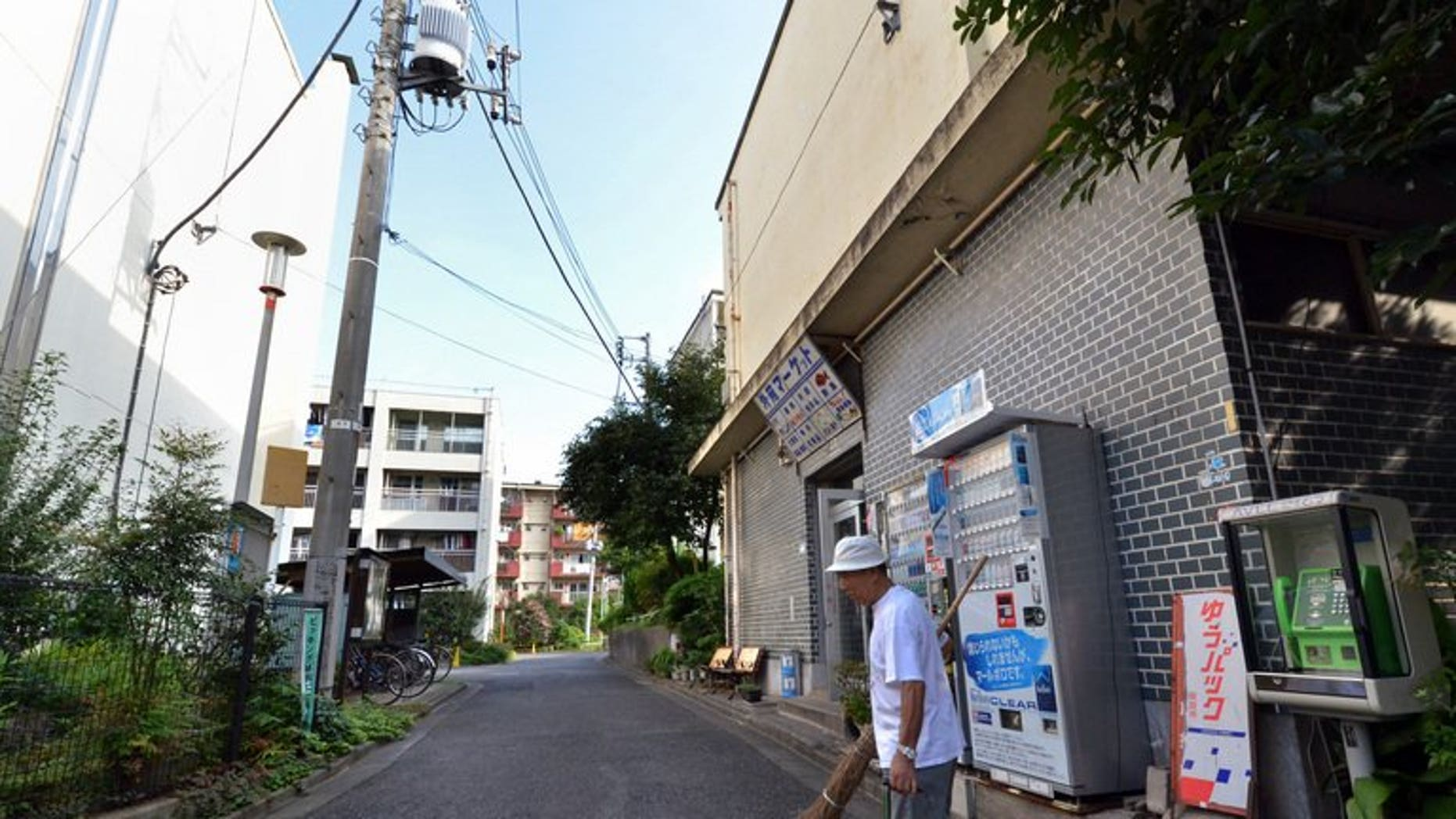 In this picture taken on September 14, 2013, 79-year-old resident Kohei Jinno sweeps and cleans a road before his apartment complex near the rebuilt national stadium in Tokyo.