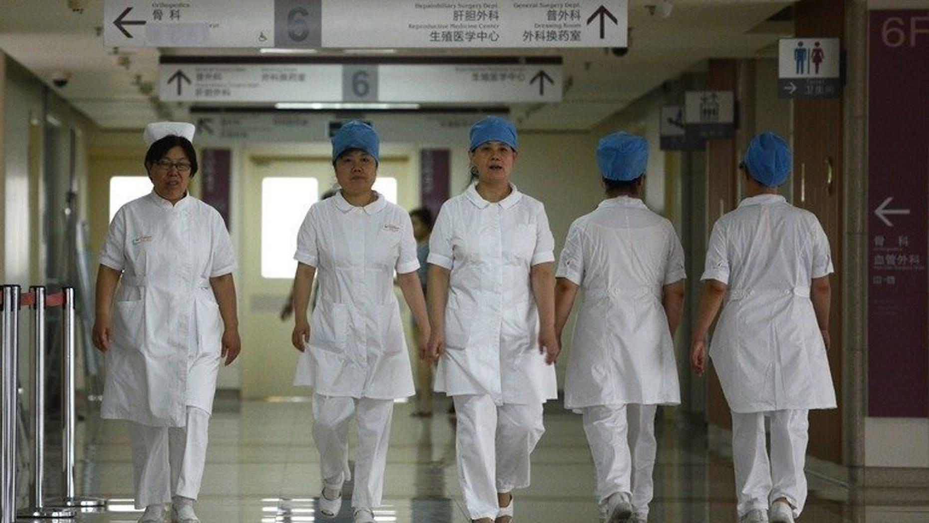 Illustration: a group of nurses walks along a corridor at a hospital in Beijing on July 29, 2013.