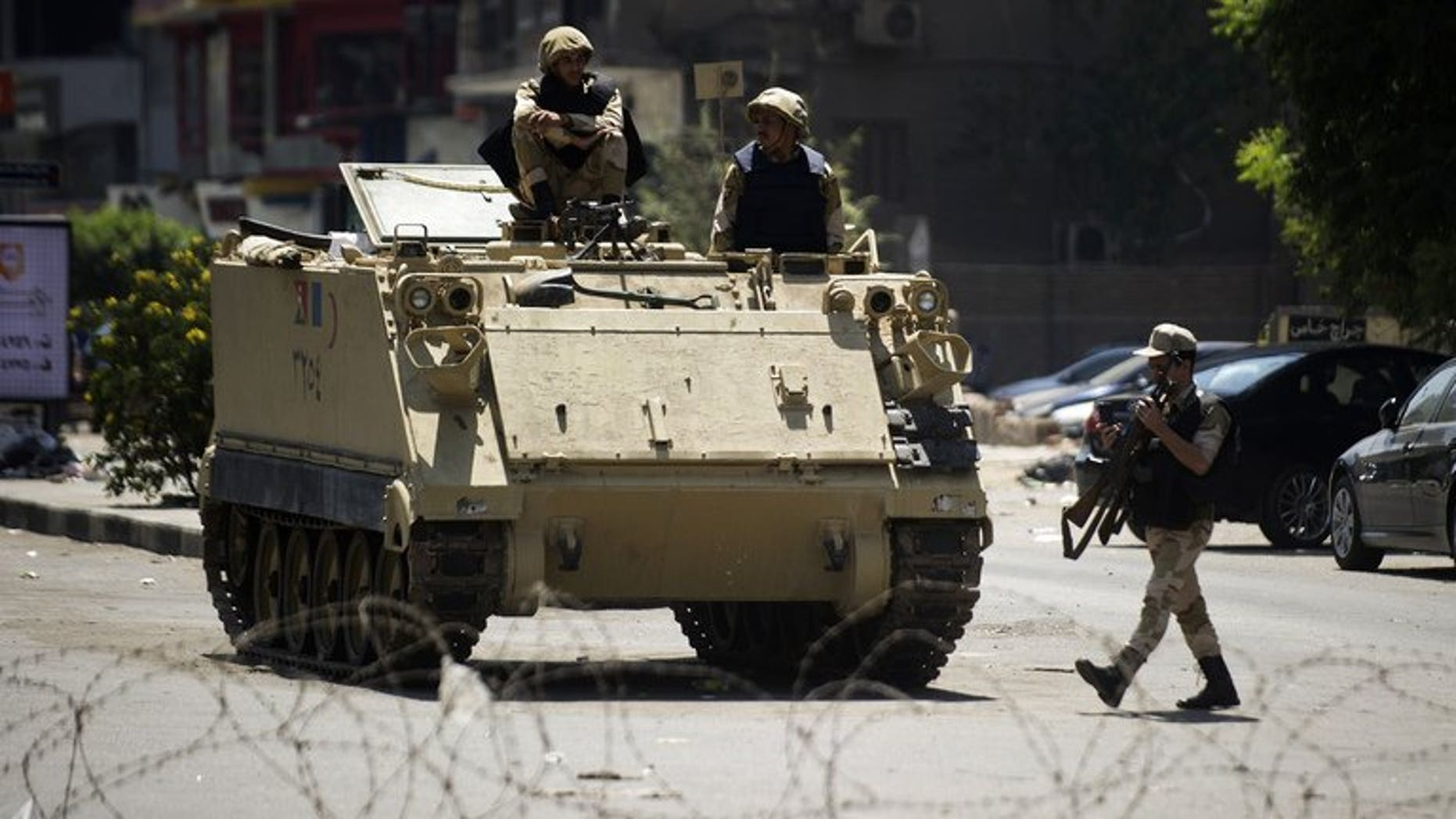 Egyptian army soldiers sit on top of an armoured personnel carrier in Cairo on August 23, 2013. Troops stormed a central Egyptian town held for over a month by hardline supporters of ousted Islamist president Mohamed Morsi who had launched a campaign against Christian residents.