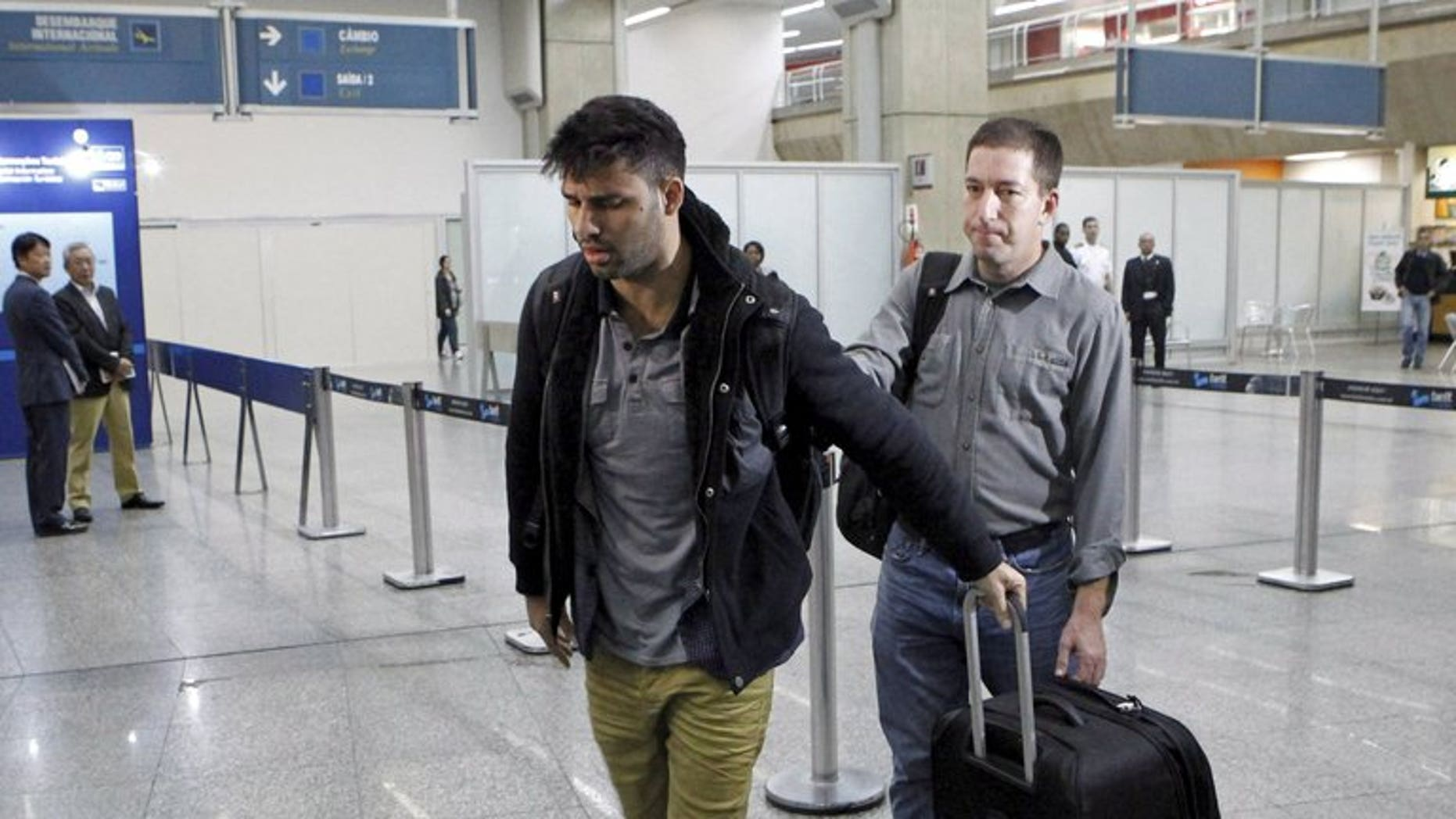 David Miranda (L), partner of Glenn Greenwald, is seen at Rio de Janeiro's Tom Jobim international airport on August 19, 2013.