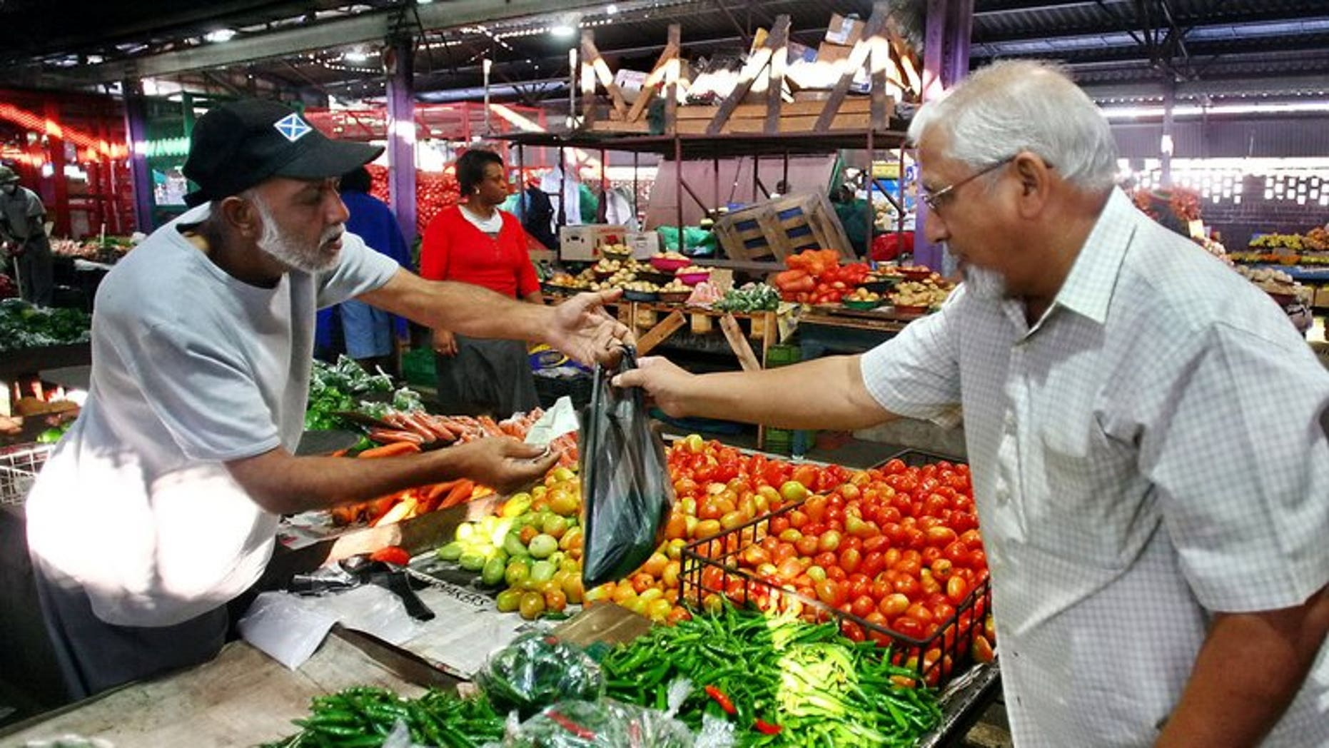A customer pays a vendor at a market in Durban on May 22, 2010. South Africa's annual inflation rate rose to 6.4 percent in August, official figures showed, well above the central bank's target.