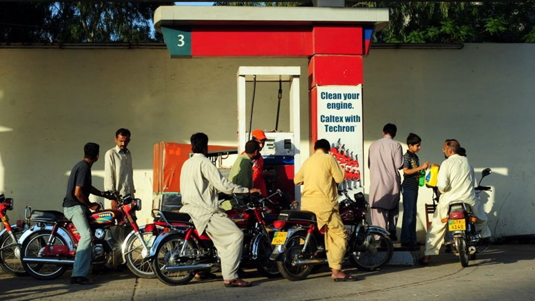 Pakistani motorcyclists gather around an oil filling point at a petrol station in Gujrat on April 15, 2011. French energy giant Total and its Pakistani partner PARCO said Wednesday they had reached a deal with American oil major Chevron to buy its fuel distribution network in Pakistan.