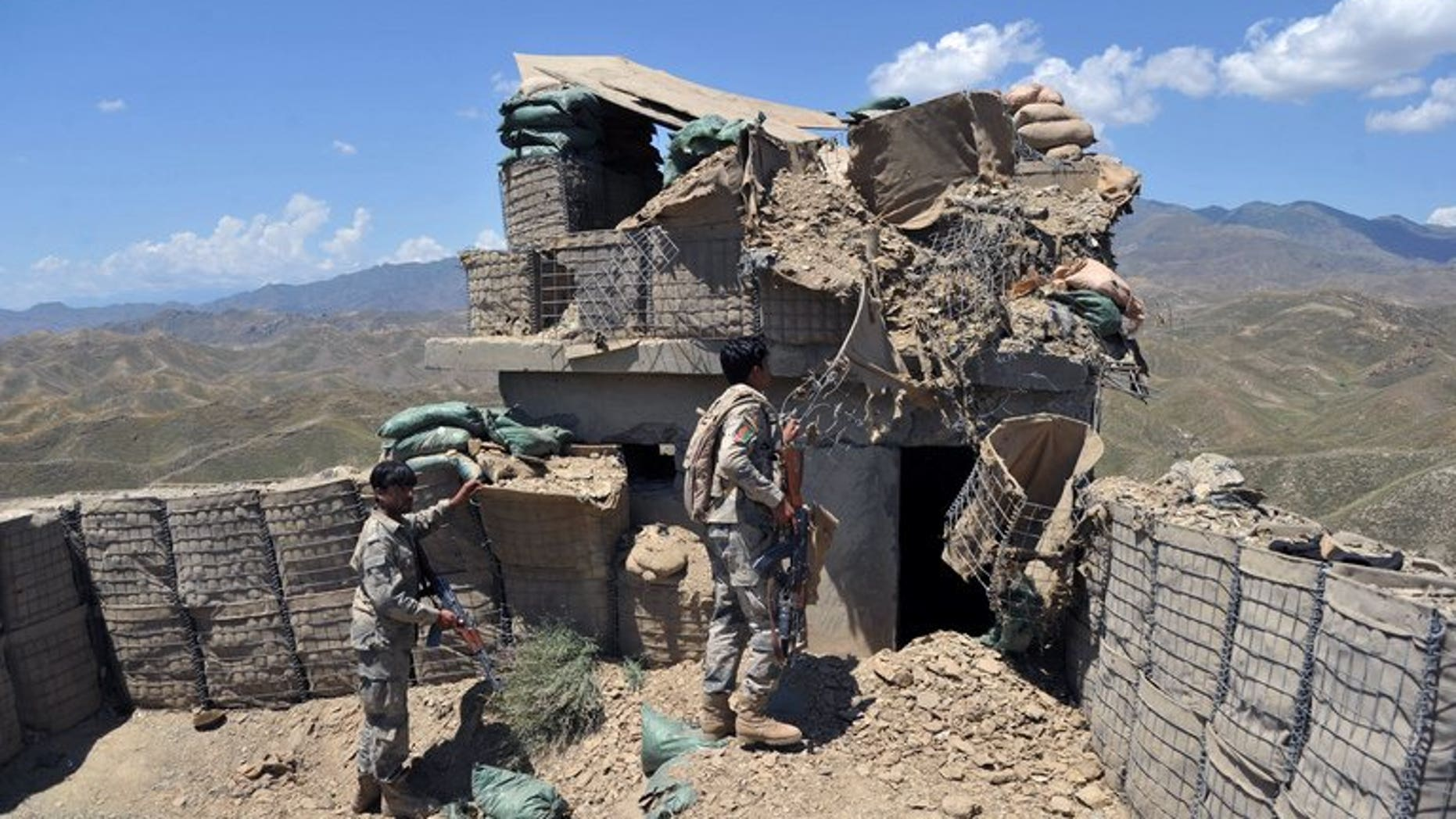 """Afghan border policemen inspect a bunker destroyed during clashes between Afghan border police and Pakistani troops in Goshta district of Nangarhar province on May 8, 2013. Pakistan accused Afghan forces of killing five Pakistanis on Wednesday in cross-border """"indiscriminate firing"""" in its southwestern Baluchistan province."""
